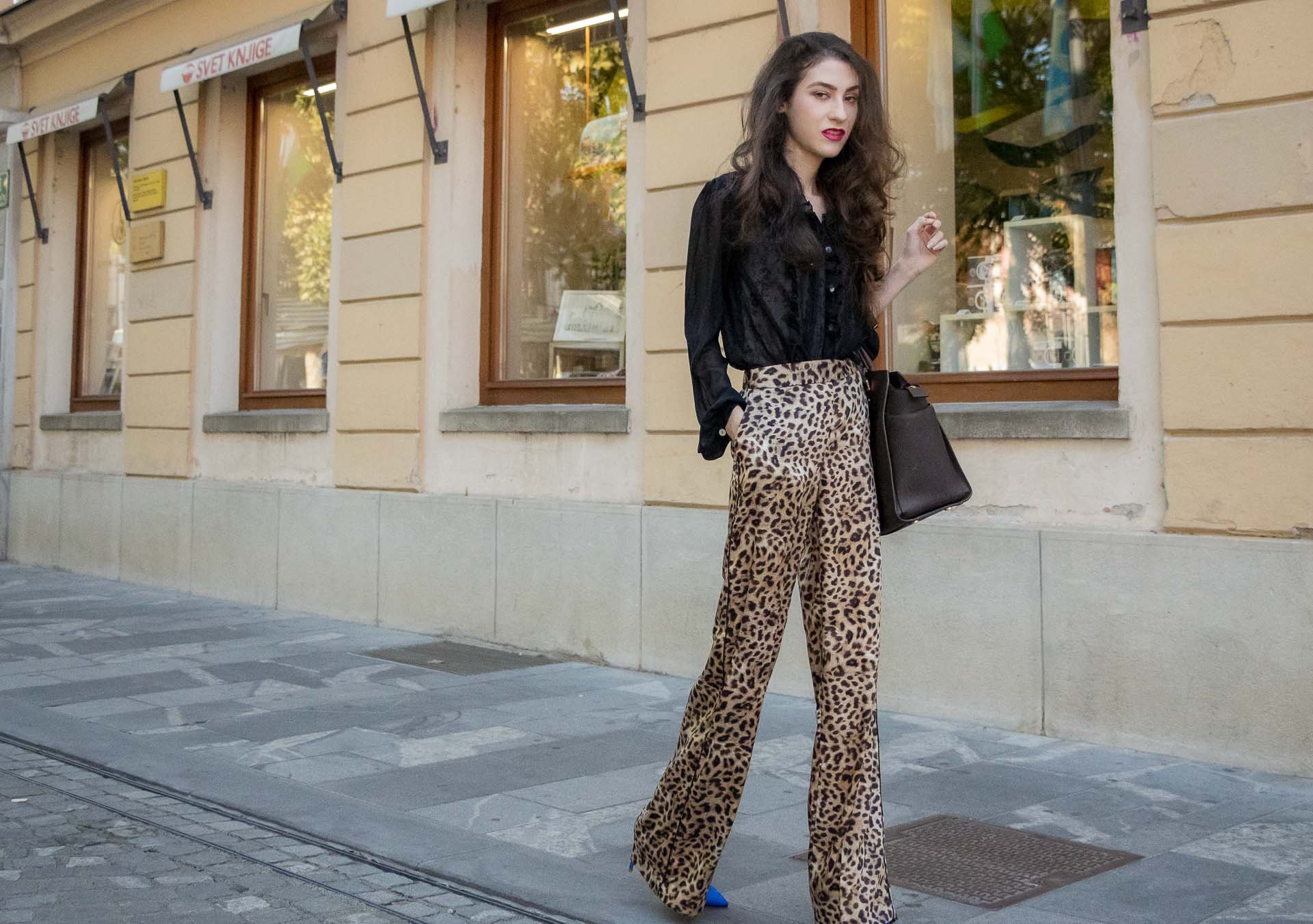 Beautiful Slovenian Fashion Blogger Veronika Lipar of Brunette from Wall dressed in black sheer blouse, Zara leopard print wide-leg pants, blue Gianvito Rossi satin pumps, brown Michael Kors Selma tote bag, on her way to work