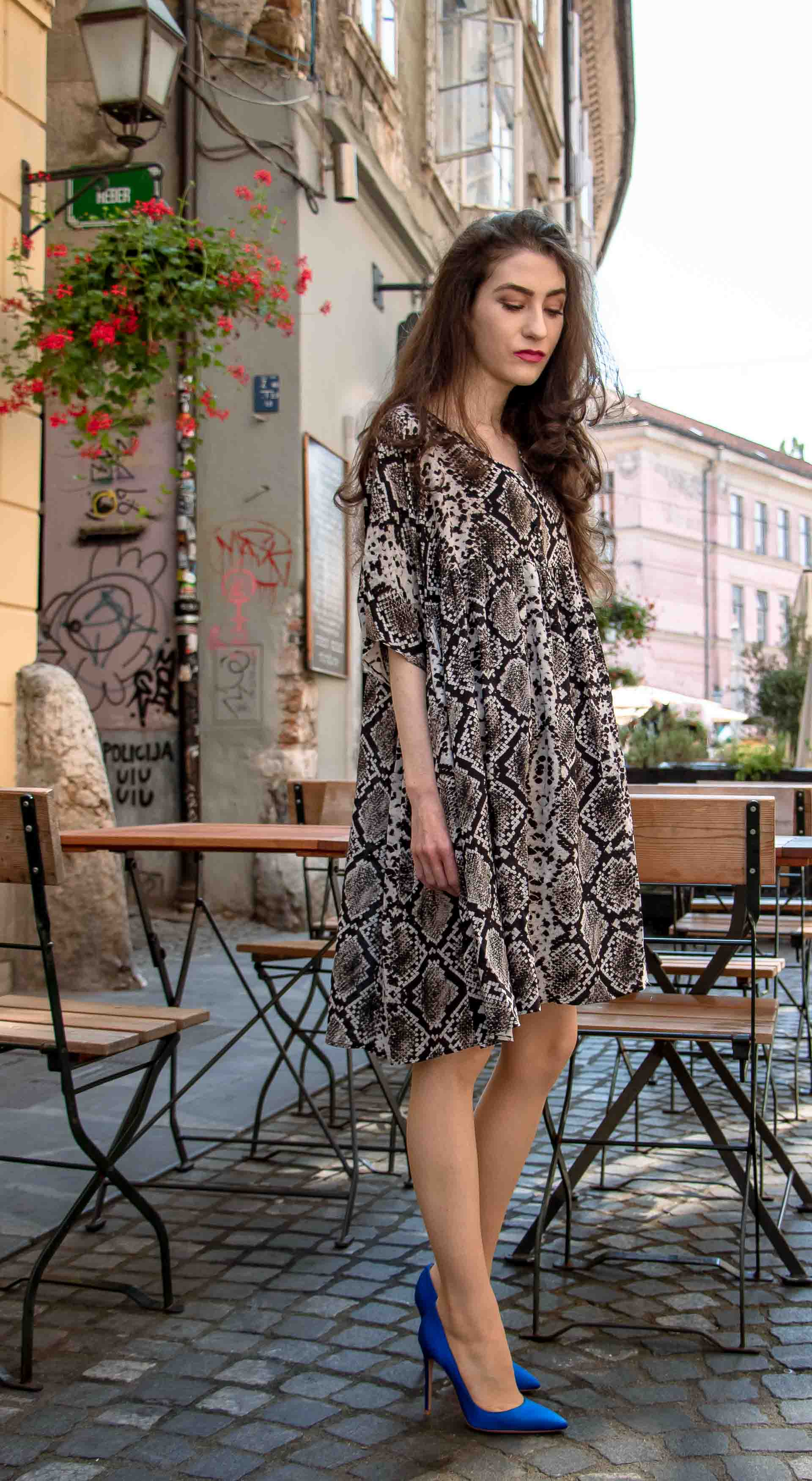 Beautiful Slovenian Fashion Blogger Veronika Lipar of Brunette from Wall dressed in flowing short snake print dress from Zara, blue Gianvito Rossi satin pumps, standing by the table on the street