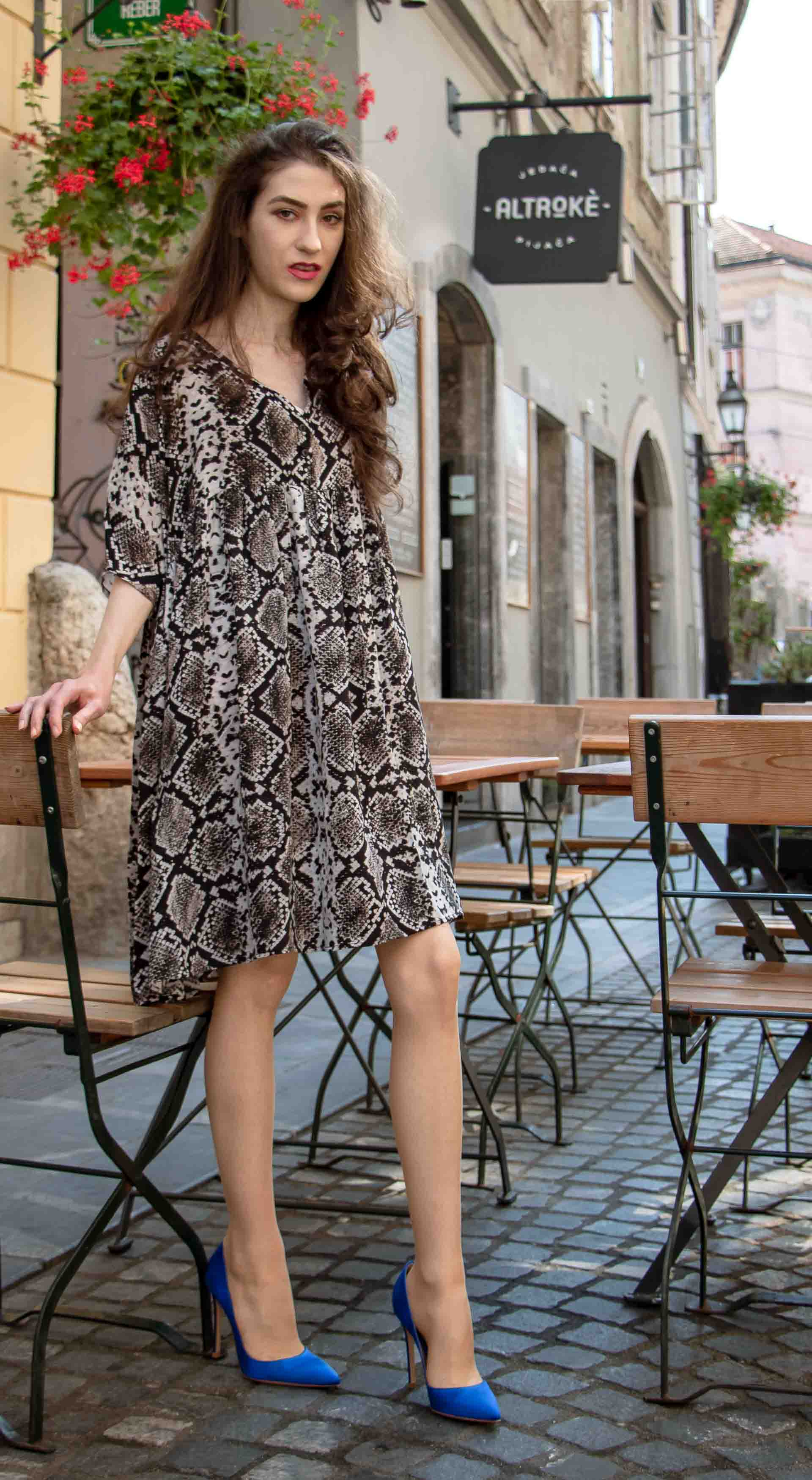 Beautiful Slovenian Fashion Blogger Veronika Lipar of Brunette from Wall wearing flowing short snake print dress from Zara, blue Gianvito Rossi satin pumps, standing by the table on the street