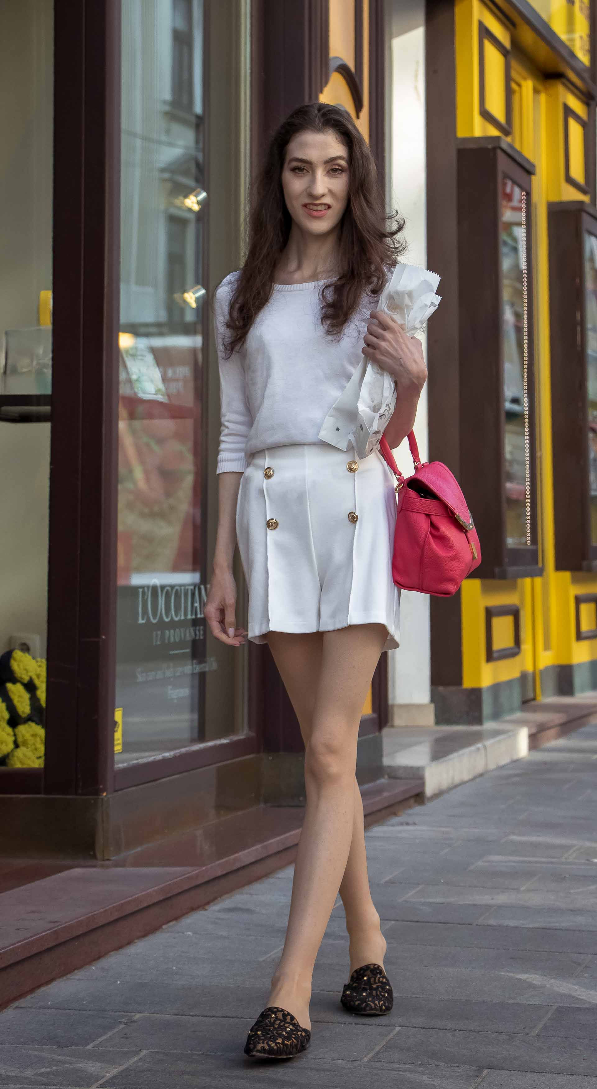 Slovenska modna blogerka Veronika Lipar of Brunette from Wall wearing all in white outfit, a white sweater, white tailored shorts, black flat slipper mules, pink top handle bag, a paper bag while walking down the street in Ljubljana