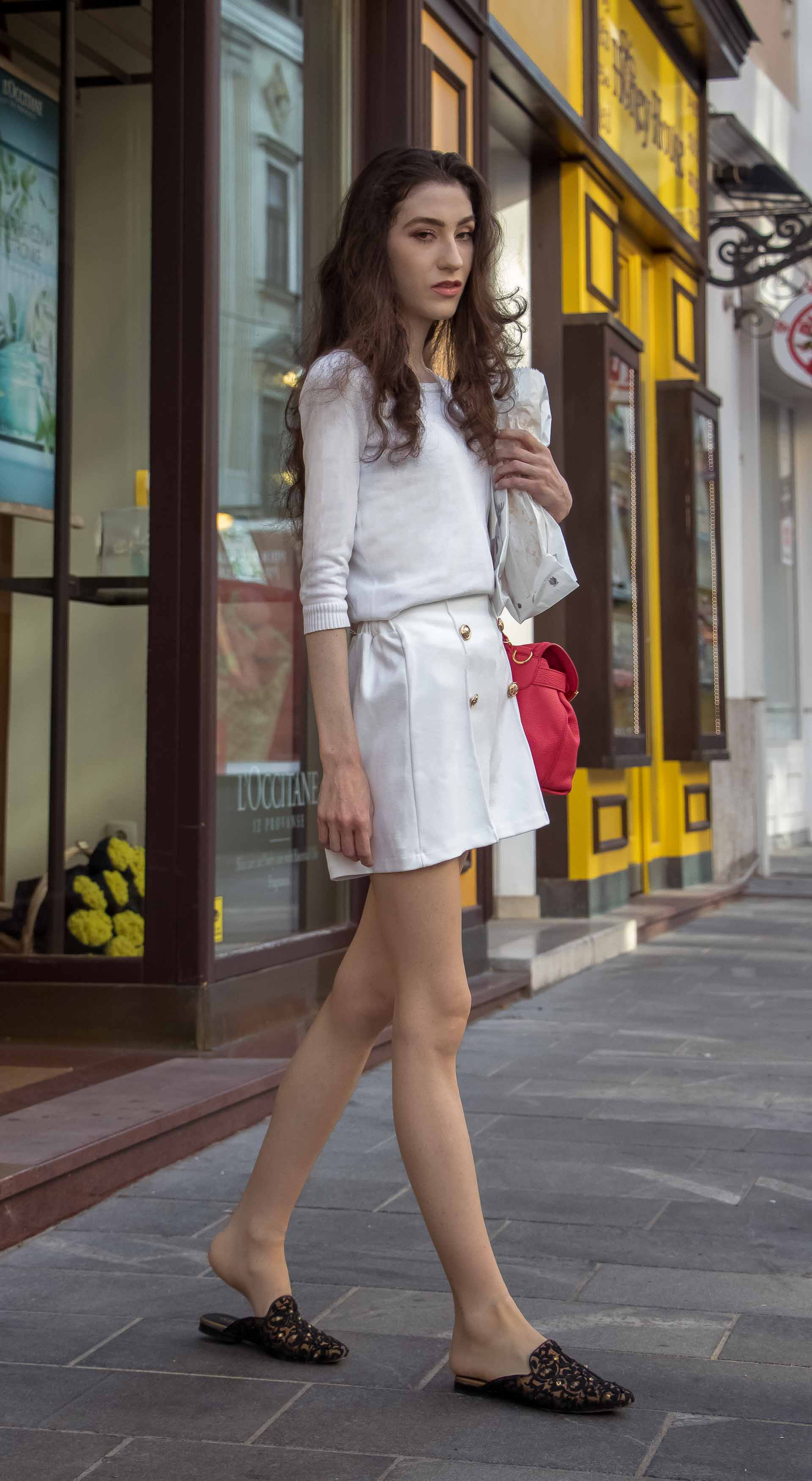 Slovenska modna blogerka Veronika Lipar of Brunette from Wall wearing all in white outfit, a white sweater, white tailored shorts, black flat slipper mules, pink top handle bag, a paper bag while standing on the street in Ljubljana