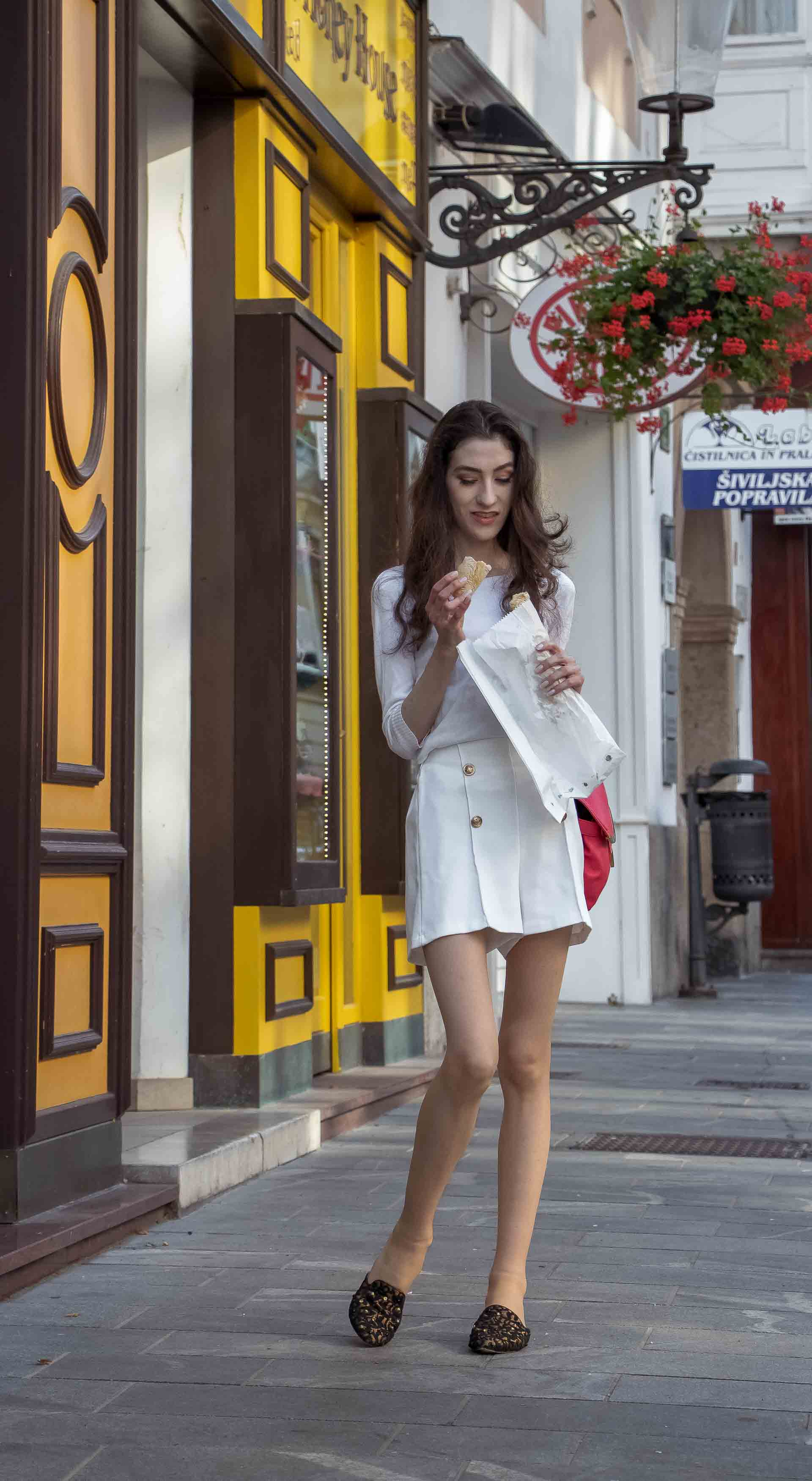 Slovenska modna blogerka Veronika Lipar of Brunette from Wall wearing all in white outfit, a white sweater, white tailored shorts, black flat slipper mules, pink top handle bag, a paper bag