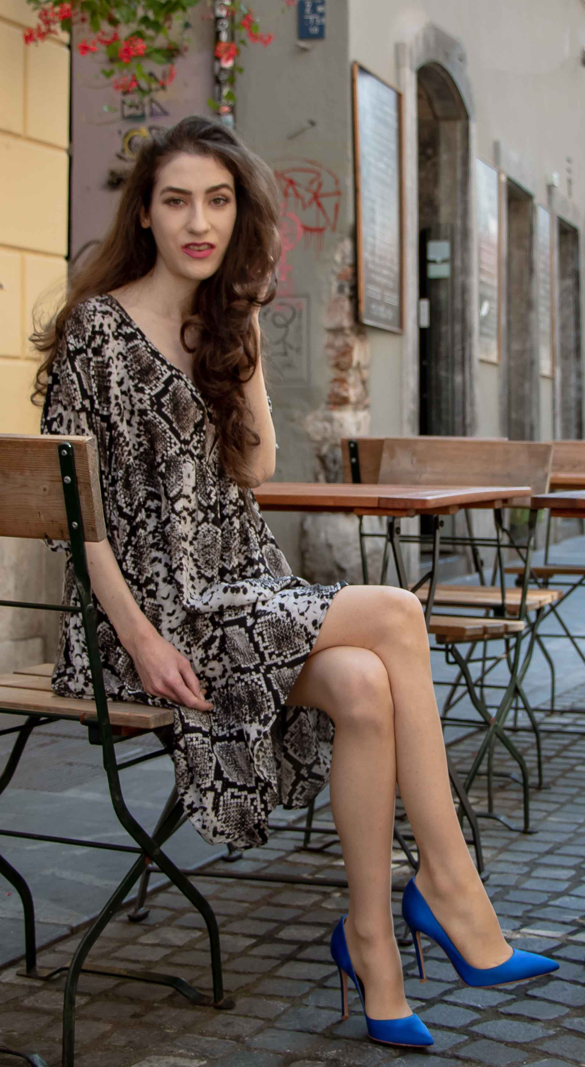 Beautiful Slovenian Fashion Blogger Veronika Lipar of Brunette from Wall dressed in flowing short snake print dress from Zara, blue Gianvito Rossi satin pumps, sitting on the street