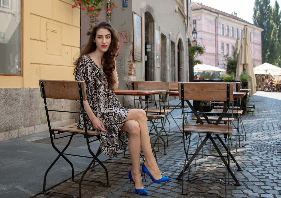 Beautiful Slovenian Fashion Blogger Veronika Lipar of Brunette from Wall wearing flowing short snake print dress from Zara, blue Gianvito Rossi satin pumps, sitting on the street