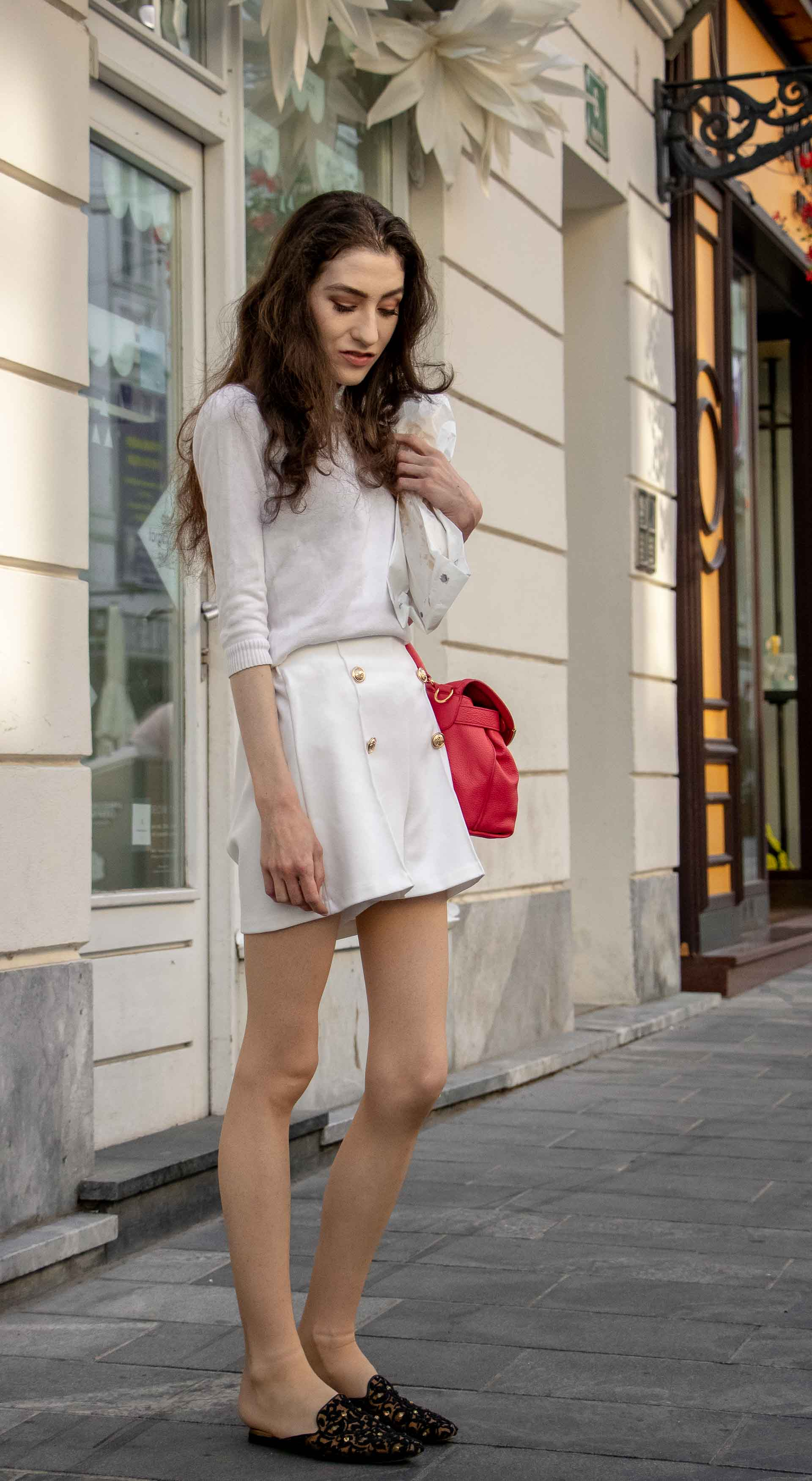 Beautiful Slovenian Fashion Blogger Veronika Lipar of Brunette from Wall wearing all in white outfit, a white sweater, white tailored shorts, black flat slipper mules, pink top handle bag, a paper bag while standing on the street in Ljubljana