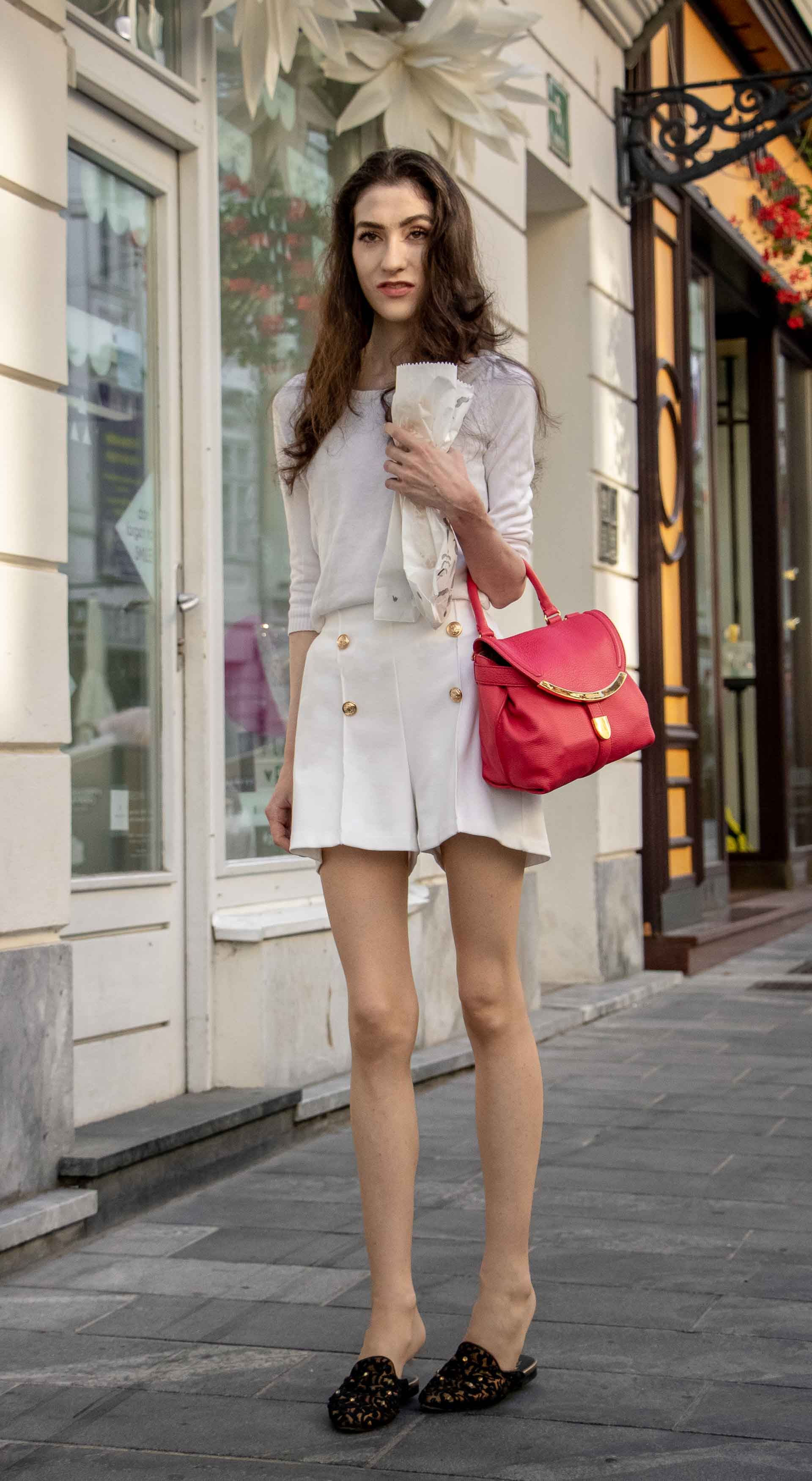 Beautiful Slovenian Fashion Blogger Veronika Lipar of Brunette from Wall dressed in all in white outfit, a white sweater, white tailored shorts, black flat slipper mules, pink top handle bag, a paper bag during heat wave in Ljubljana