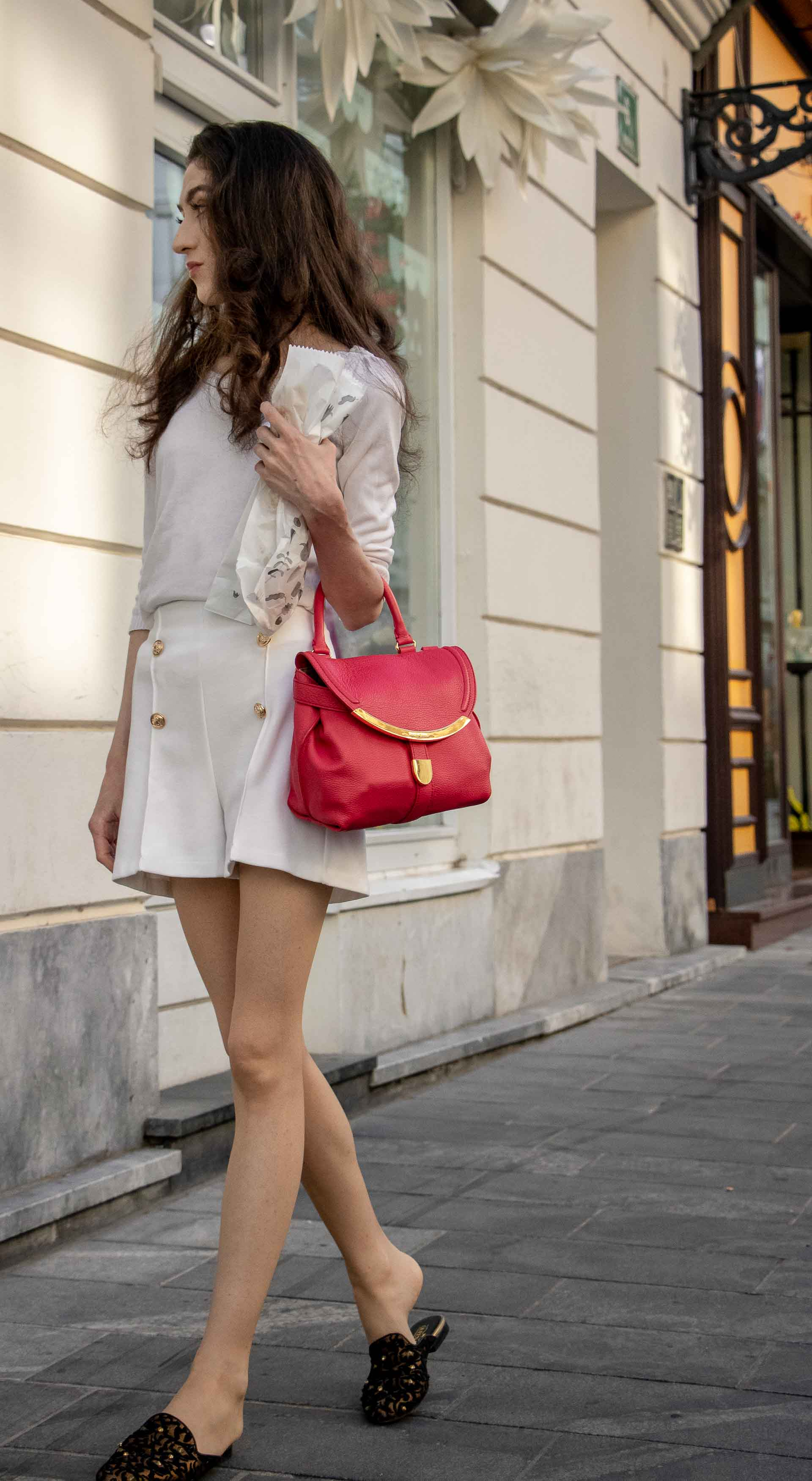 Beautiful Slovenian Fashion Blogger Veronika Lipar of Brunette from Wall dressed in all in white outfit, a white sweater, white tailored shorts, black flat slipper mules, pink top handle bag, a paper bag on the street in Ljubljana when it's hot