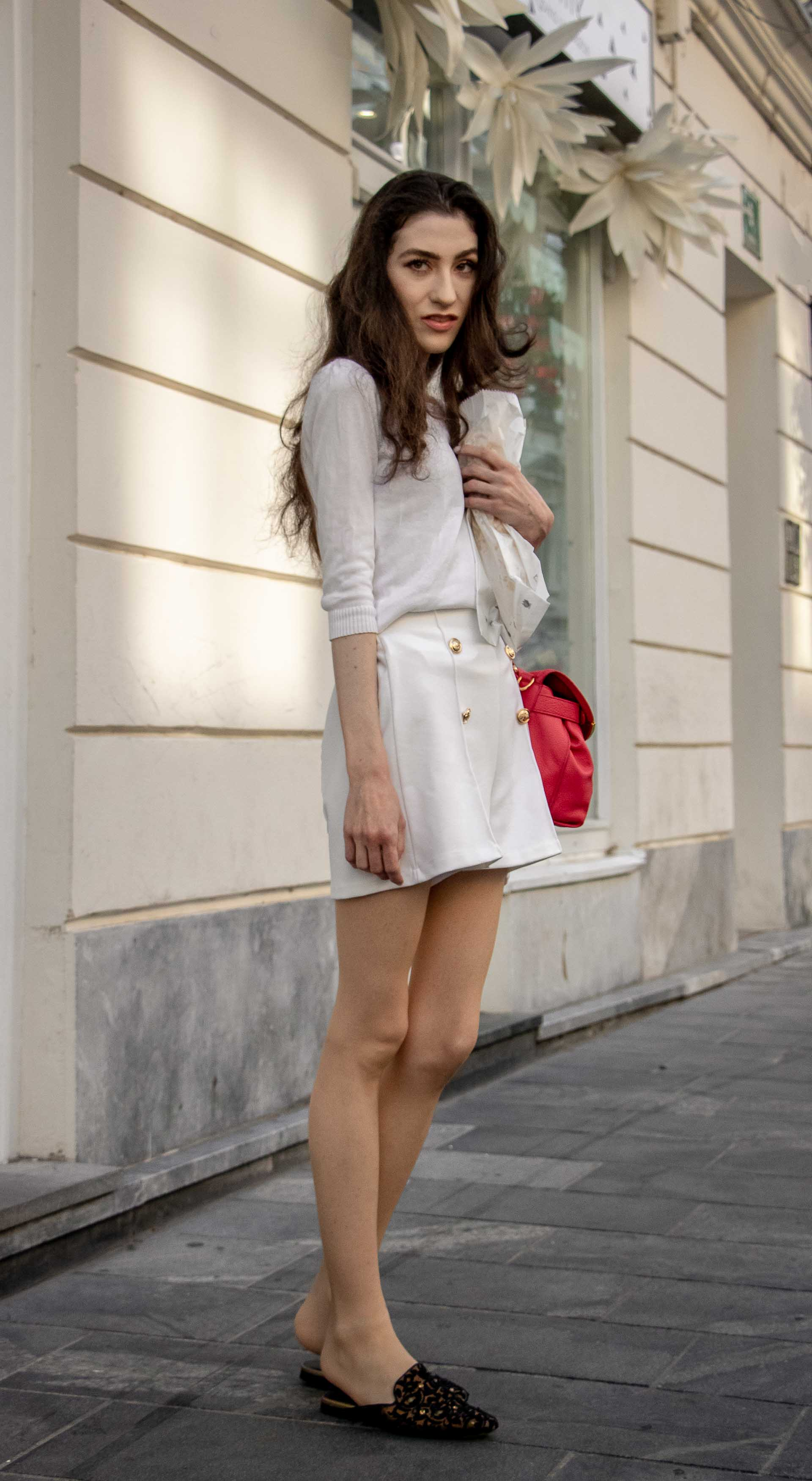 Beautiful Slovenian Fashion Blogger Veronika Lipar of Brunette from Wall dressed in all in white outfit, a white sweater, white tailored shorts, black flat slipper mules, pink top handle bag, a paper bag in summer in the city