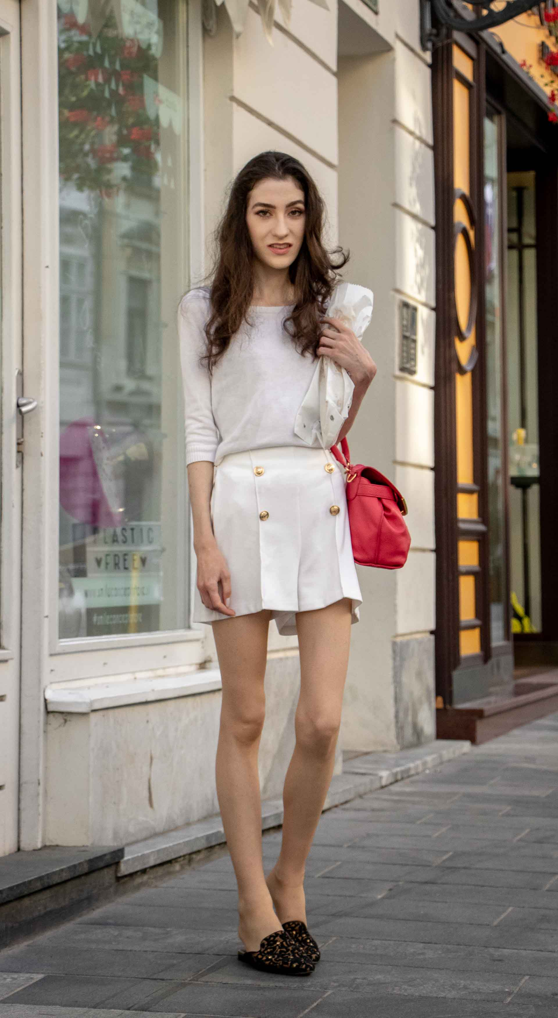 Beautiful Slovenian Fashion Blogger Veronika Lipar of Brunette from Wall wearing all in white outfit, a white sweater, white tailored shorts, black flat slipper mules, pink top handle bag, a paper bag on the street in Ljubljana during heatwave