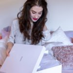 Beautiful Slovenian Fashion Blogger Veronika Lipar of Brunette from Wall dressed in white silk shirt, blue jeans, sitting on the bed while unboxing white box