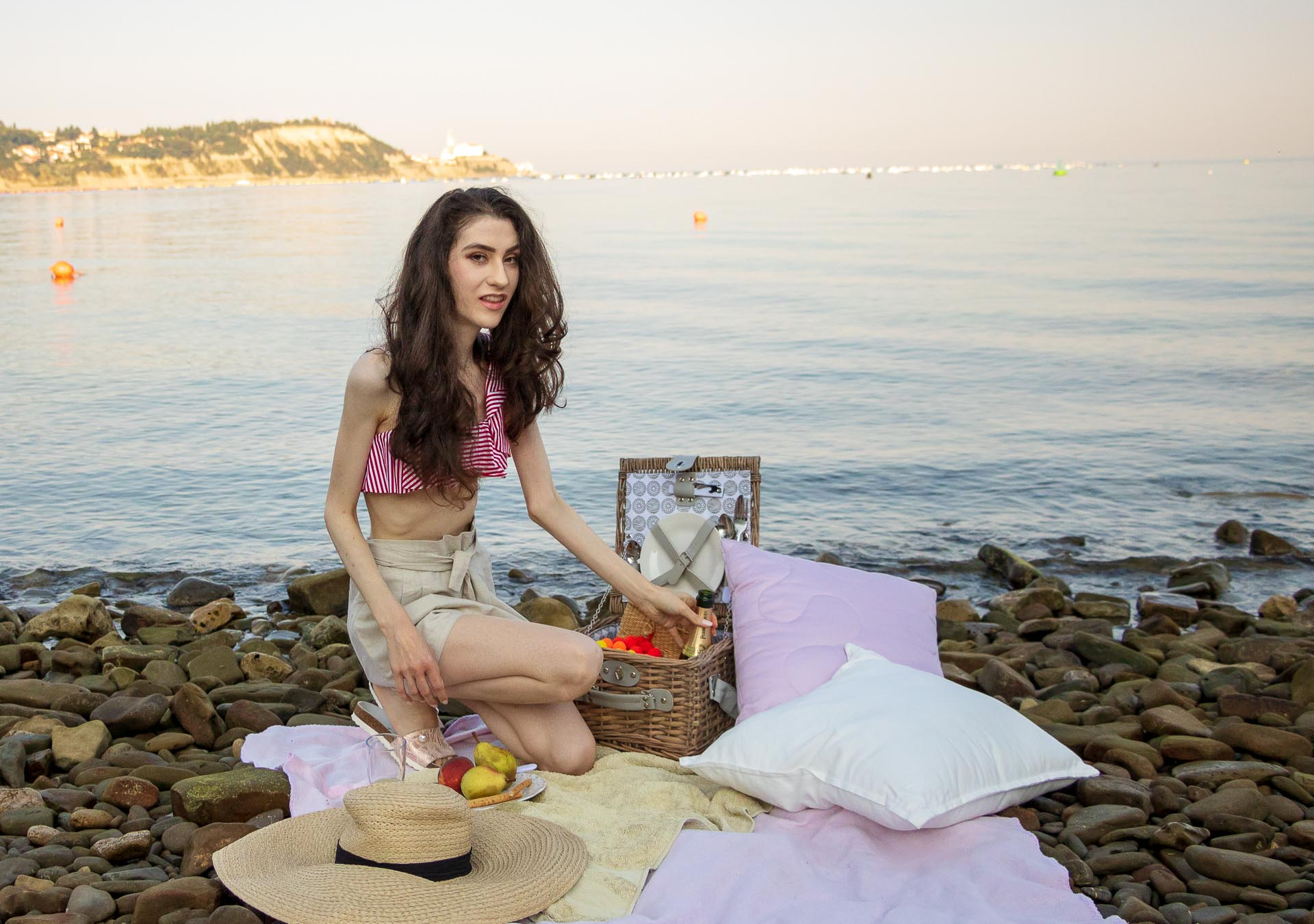 Slovenian Fashion Blogger Veronika Lipar of Brunette from Wall wearing beige linen crop top, paper bag linen shorts, luxe pool slides, large straw hat, Nannacay basket bag while taking picnic food out of the picnic basket