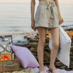Slovenian Fashion Blogger Veronika Lipar of Brunette from Wall wearing beige linen crop top, paper bag linen shorts, luxe pool slides, large straw hat, Nannacay basket bag while holding a pillow at beach picnic