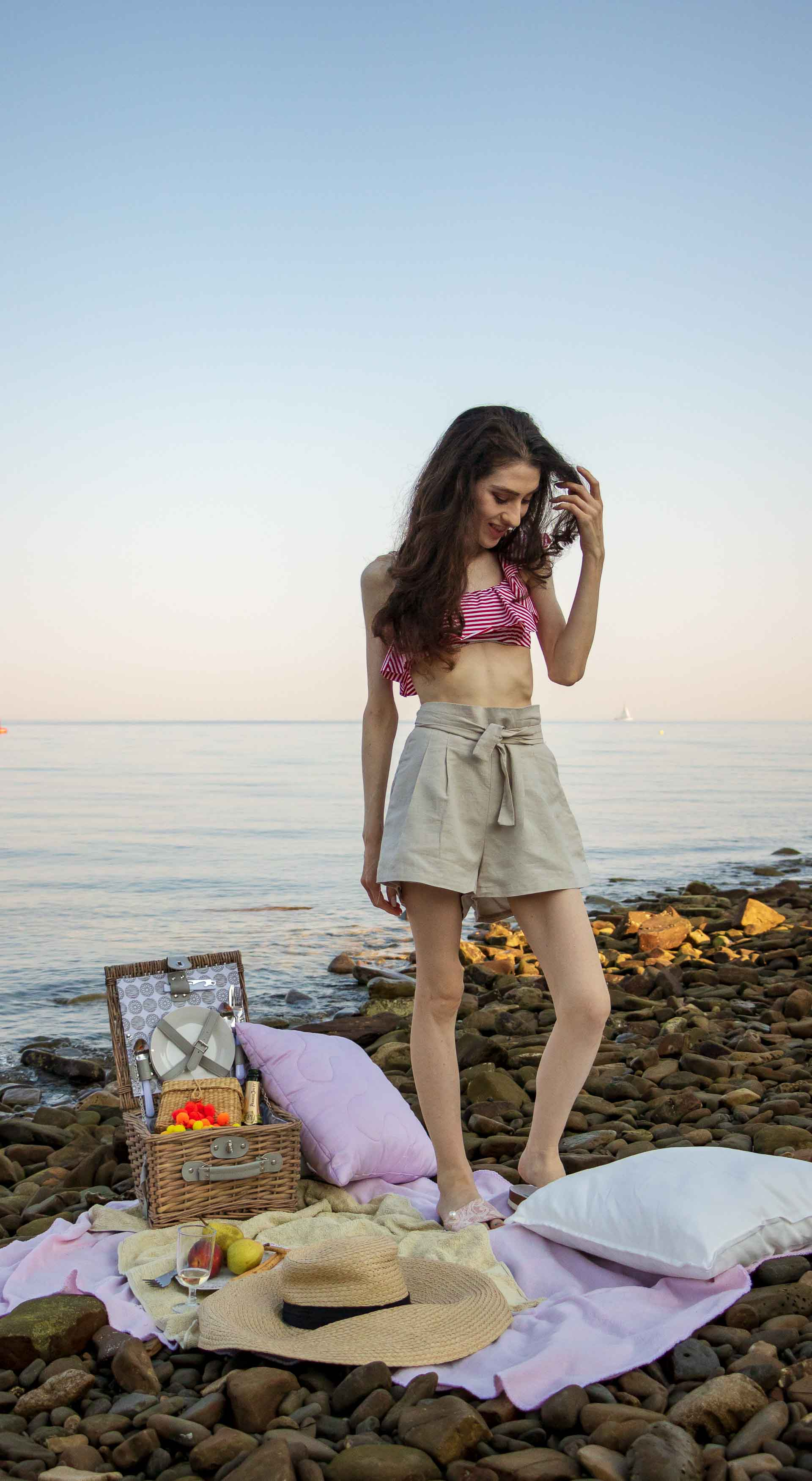 Slovenian Fashion Blogger Veronika Lipar of Brunette from Wall wearing beige linen crop top, paper bag linen shorts, luxe pool slides, large straw hat, Nannacay basket bag while standing on the picnic blanket on the beach