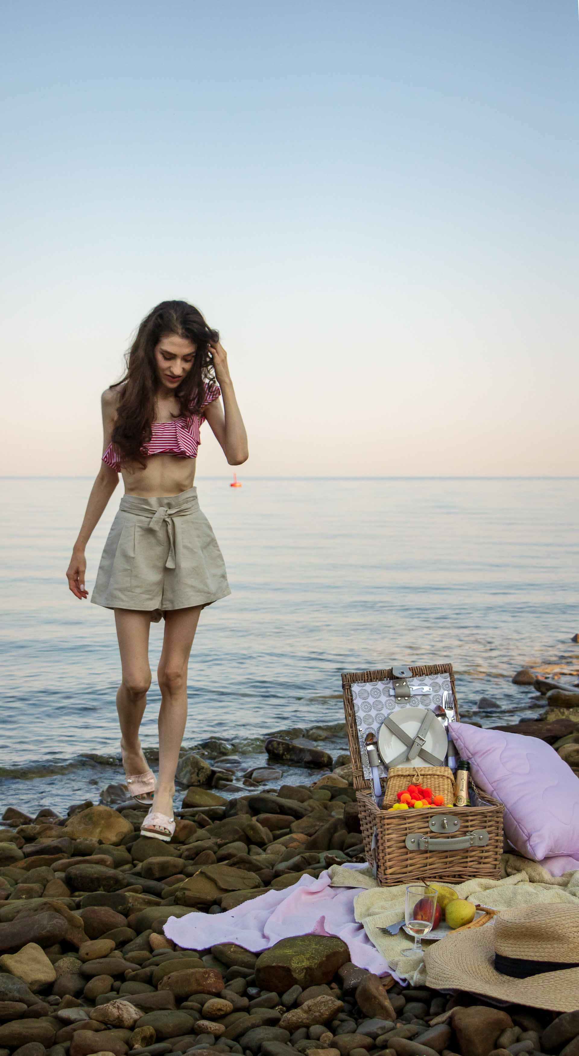 Slovenian Fashion Blogger Veronika Lipar of Brunette from Wall dressed in beige linen crop top, paper bag linen shorts, luxe pool slides, large straw hat, Nannacay basket bag while walking from the sea to the picnic spot on the beach