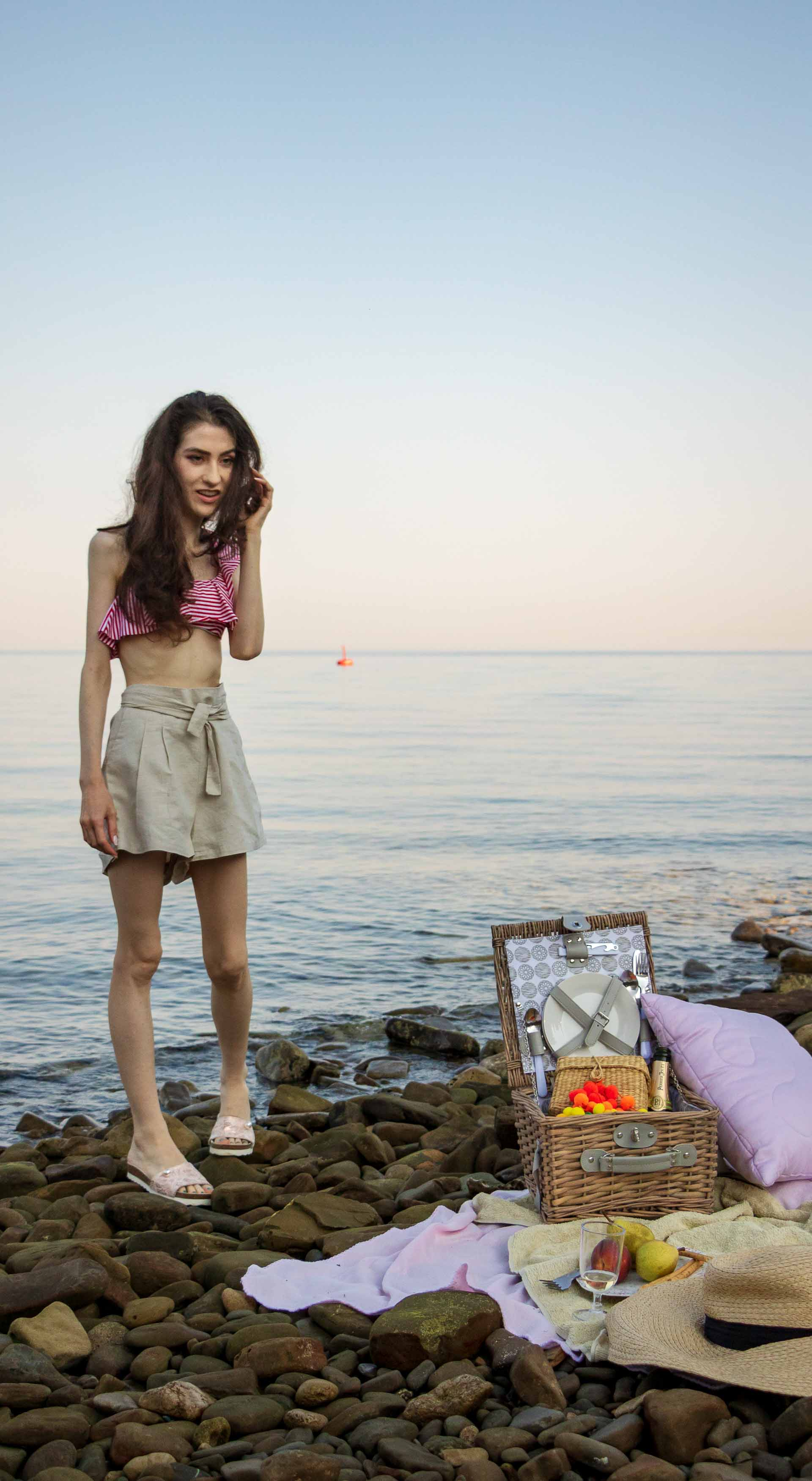 Slovenian Fashion Blogger Veronika Lipar of Brunette from Wall wearing beige linen crop top, paper bag linen shorts, luxe pool slides, large straw hat, Nannacay basket bag while walking to the picnic blanket on the beach