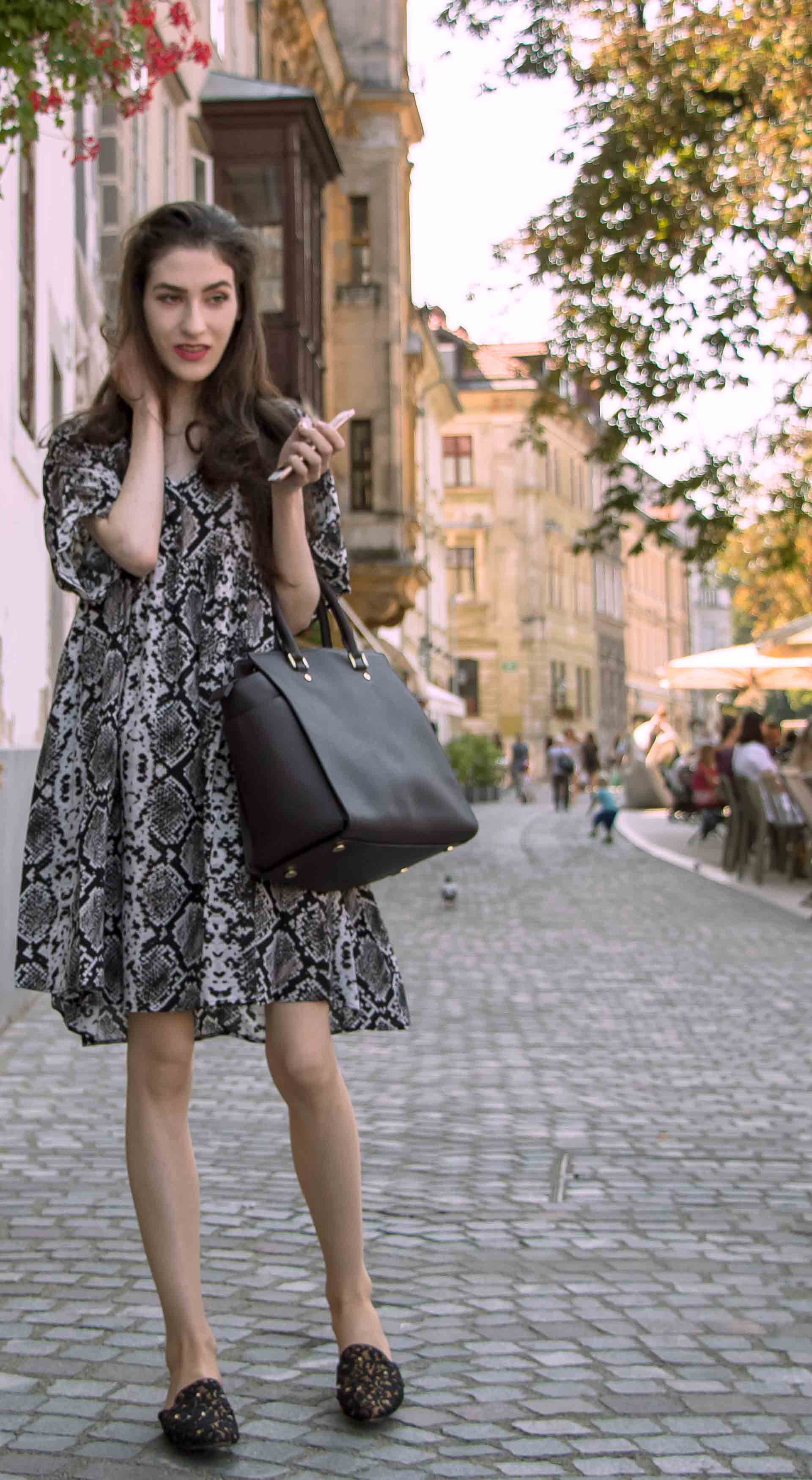 Beautiful Slovenian Fashion Blogger Veronika Lipar of Brunette from Wall dressed in boho chic flowing short snake print dress from Zara, black flat mules standing on the street in Ljubljana