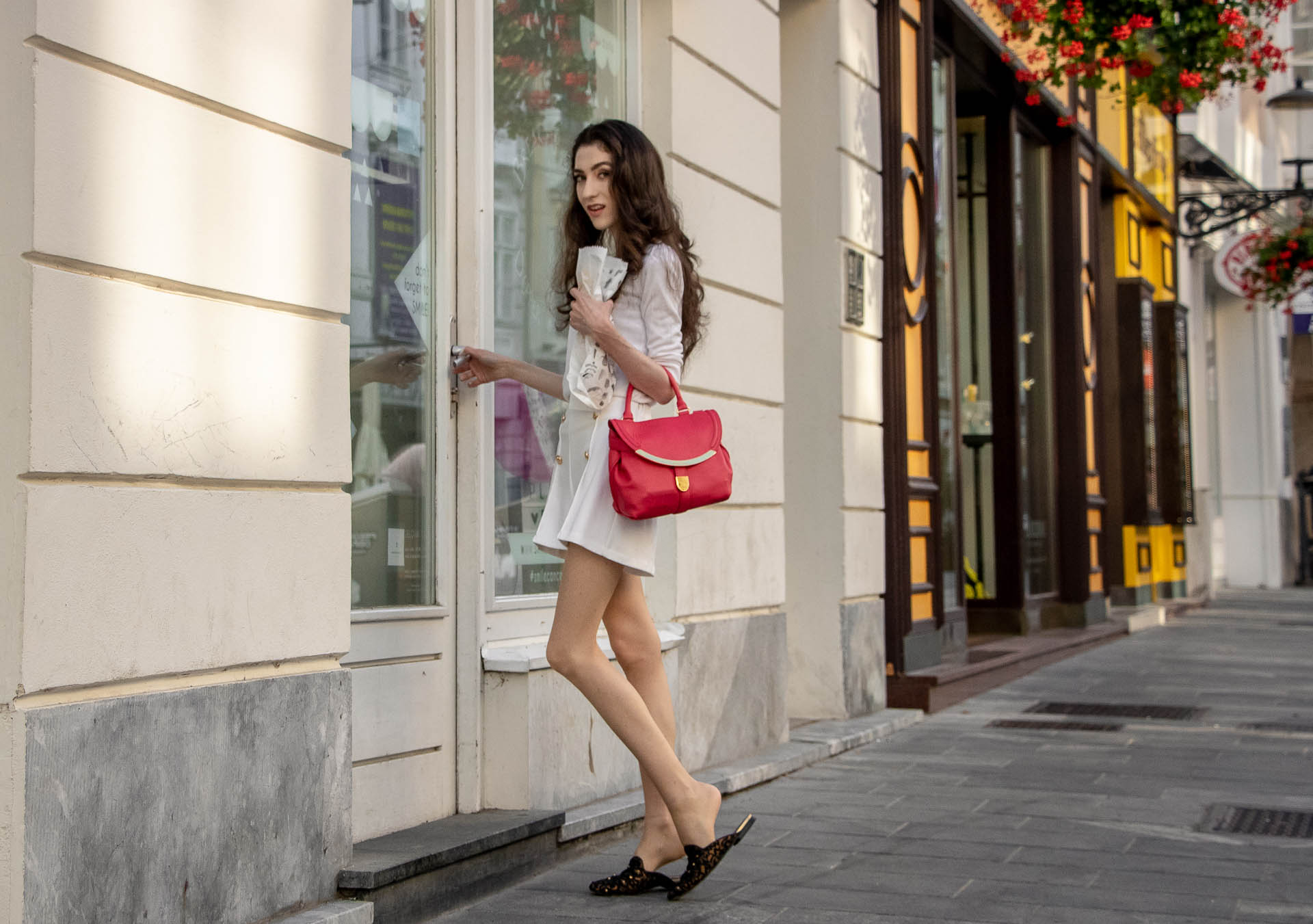 Beautiful Slovenian Fashion Blogger Veronika Lipar of Brunette from Wall wearing all in white outfit, a white sweater, white tailored shorts, black flat slipper mules, pink top handle bag, a paper bag on the street in Ljubljana when it's hot opening the doors