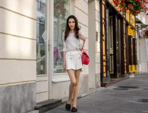 Beautiful Slovenian Fashion Blogger Veronika Lipar of Brunette from Wall wearing all in white outfit, a white sweater, white tailored shorts, black flat slipper mules, pink top handle bag, a paper bag on the street in Ljubljana when it's hot