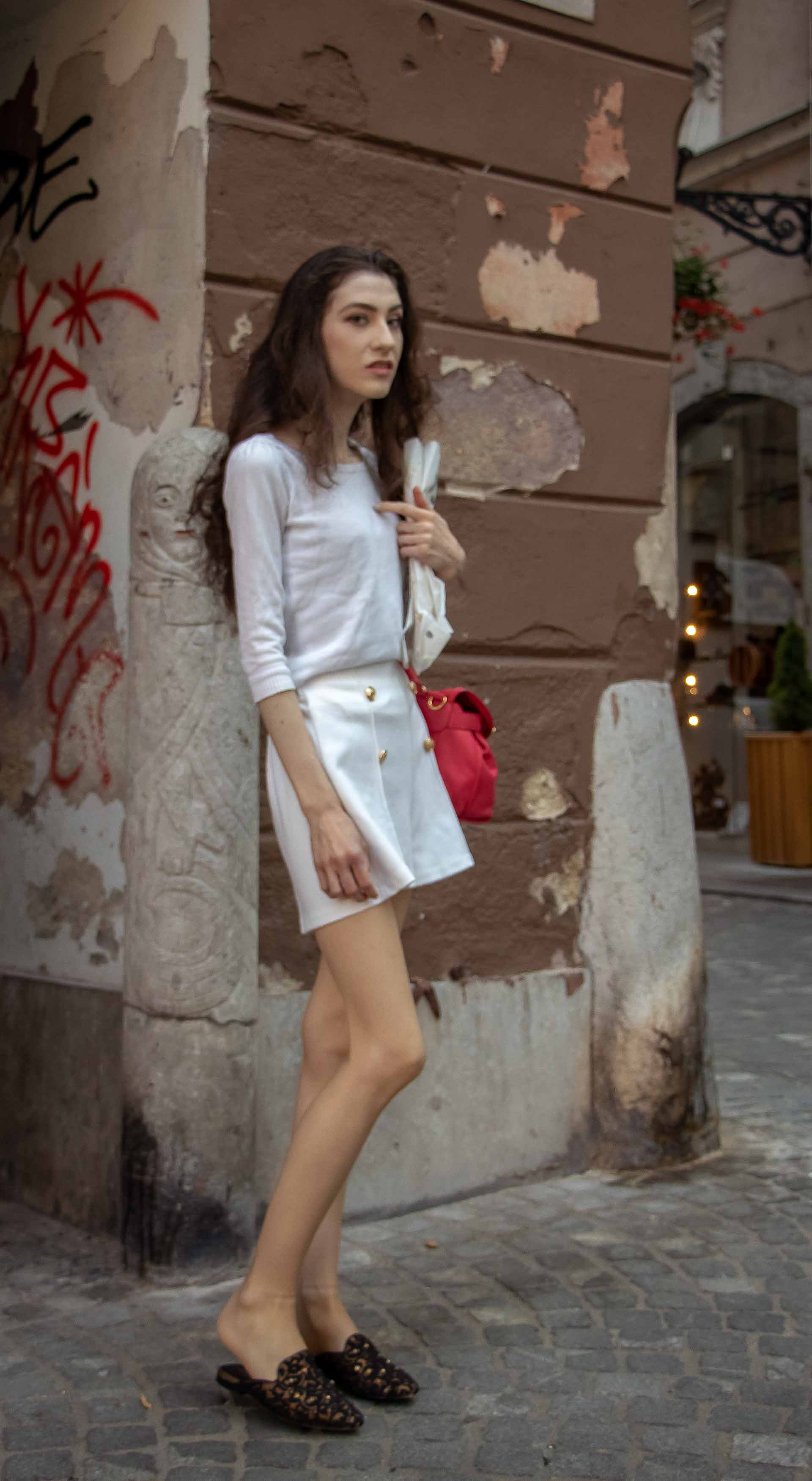 Beautiful Slovenian Fashion Blogger Veronika Lipar of Brunette from Wall dressed in all in white outfit, a white sweater, white tailored shorts, black flat slipper mules, pink top handle bag, a paper bag while standing on the street in Ljubljana