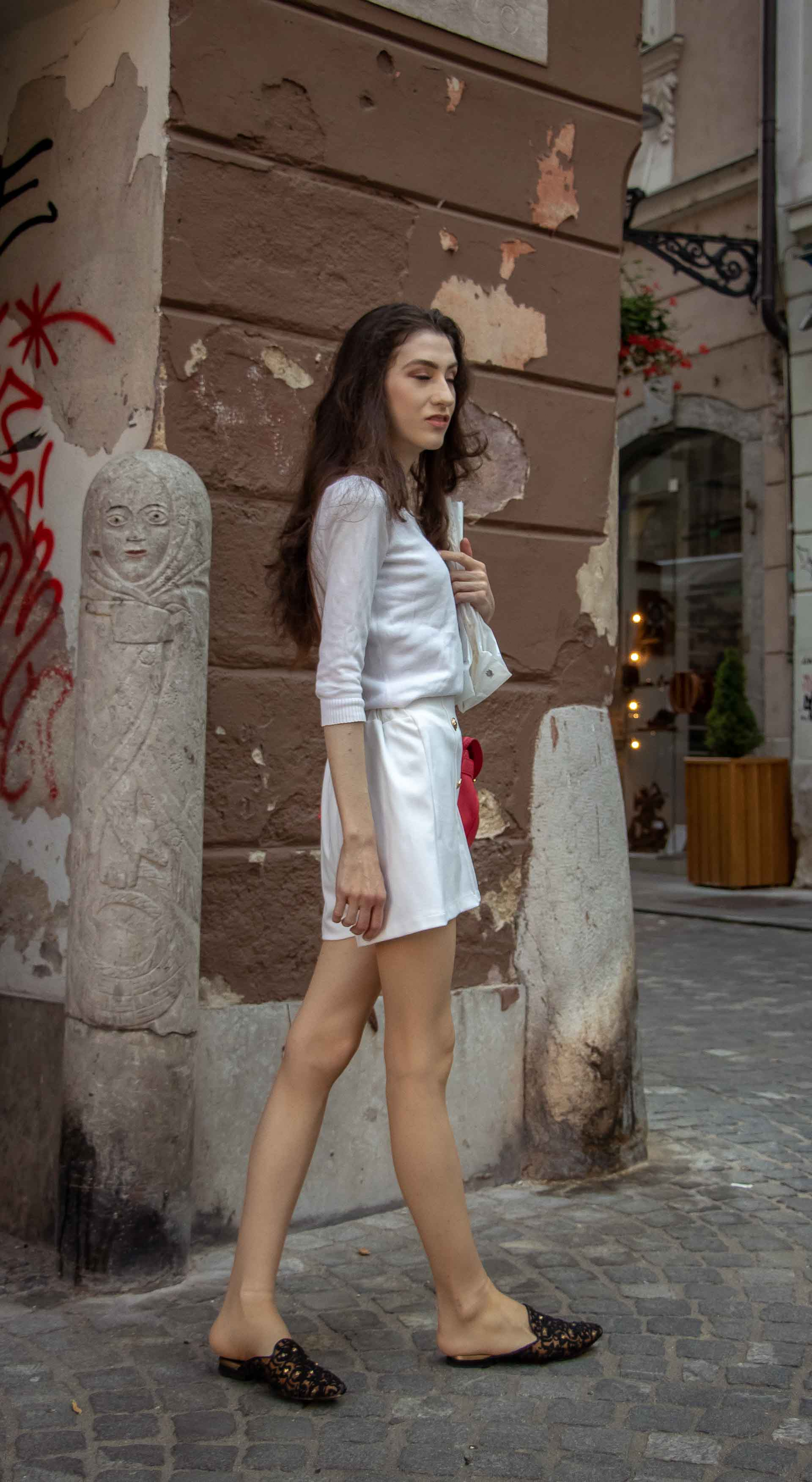 Beautiful Slovenian Fashion Blogger Veronika Lipar of Brunette from Wall dressed in all in white outfit, a white sweater, white tailored shorts, black flat slipper mules, pink top handle bag, a paper bag while walking on the street in Ljubljana