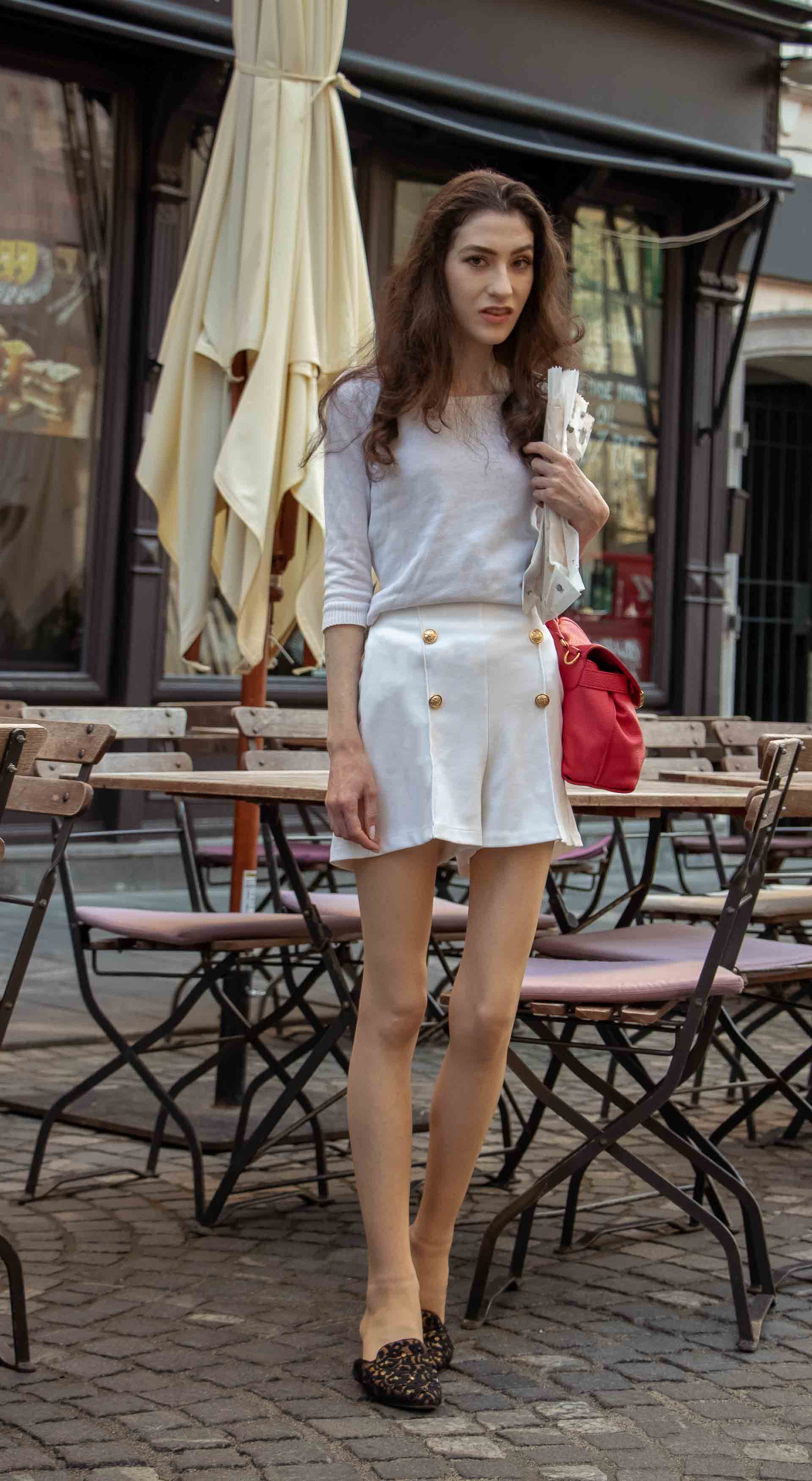Beautiful Slovenian Fashion Blogger Veronika Lipar of Brunette from Wall wearing all in white outfit, a white sweater, white tailored shorts, black flat slipper mules, pink top handle bag, a paper bag during heatwave in Ljubljana