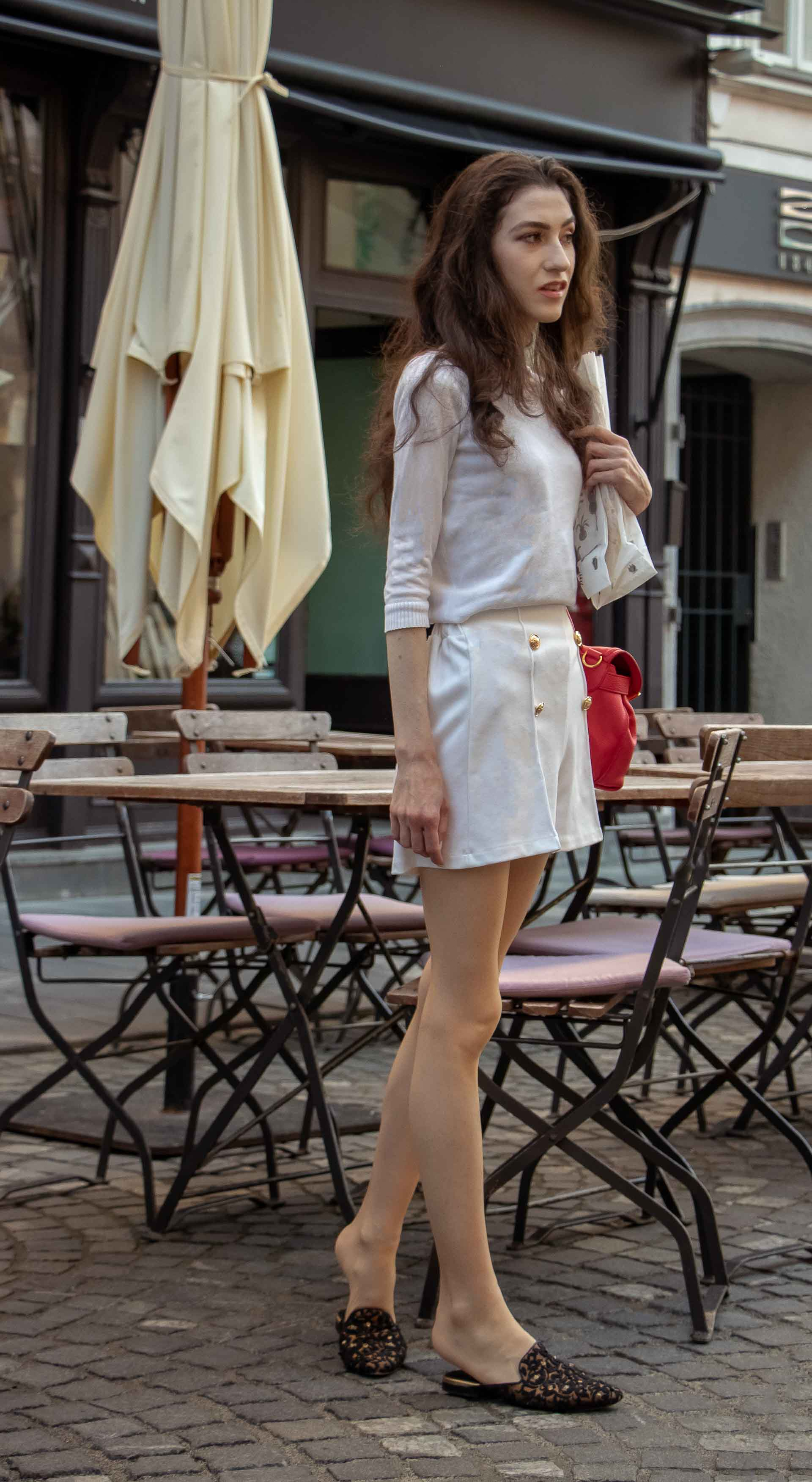 Beautiful Slovenian Fashion Blogger Veronika Lipar of Brunette from Wall wearing all in white outfit, a white sweater, white tailored shorts, black flat slipper mules, pink top handle bag, a paper bag on the street in Ljubljana