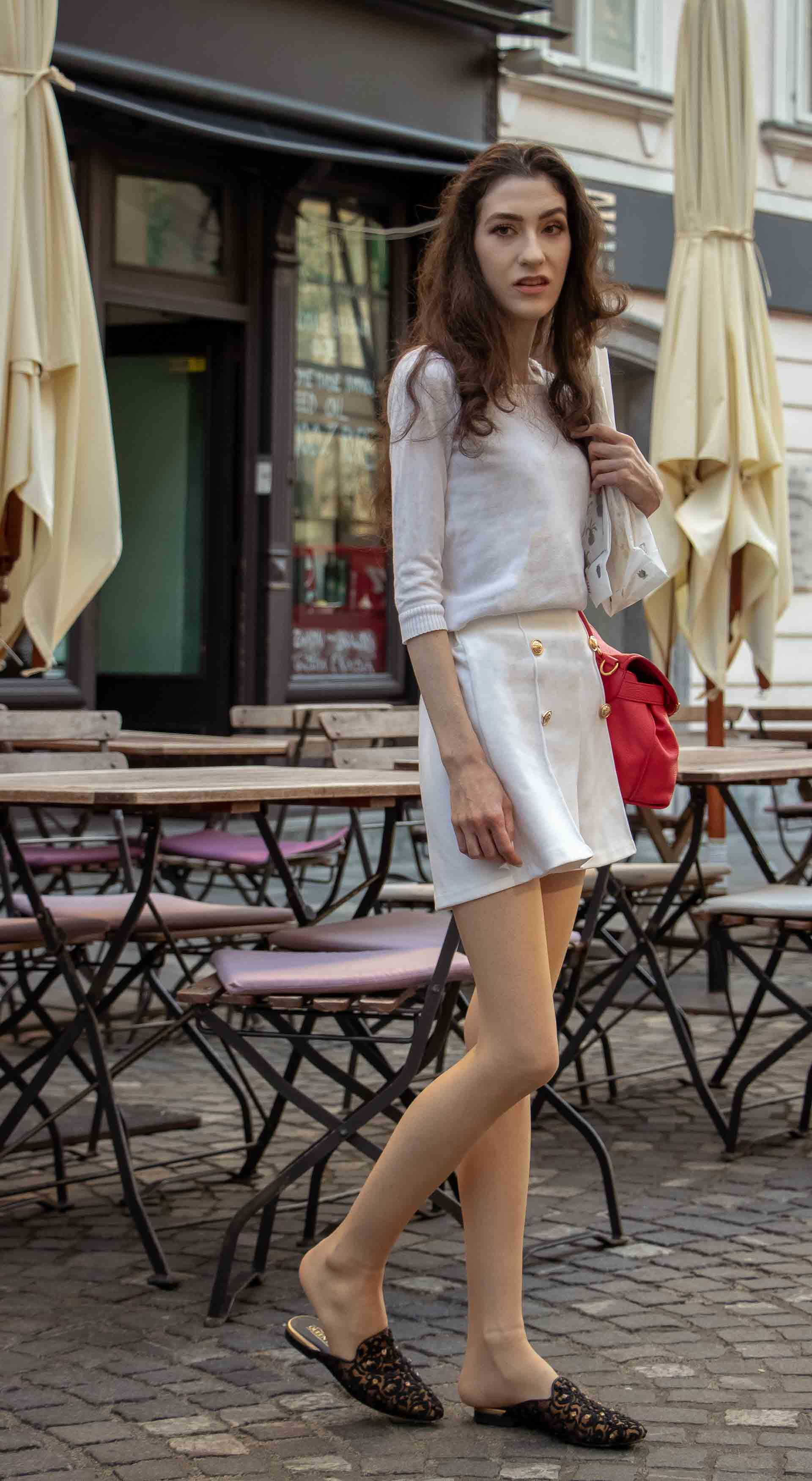 Beautiful Slovenian Fashion Blogger Veronika Lipar of Brunette from Wall wearing all in white outfit, a white sweater, white tailored shorts, black flat slipper mules, pink top handle bag, a paper bag when it's hot
