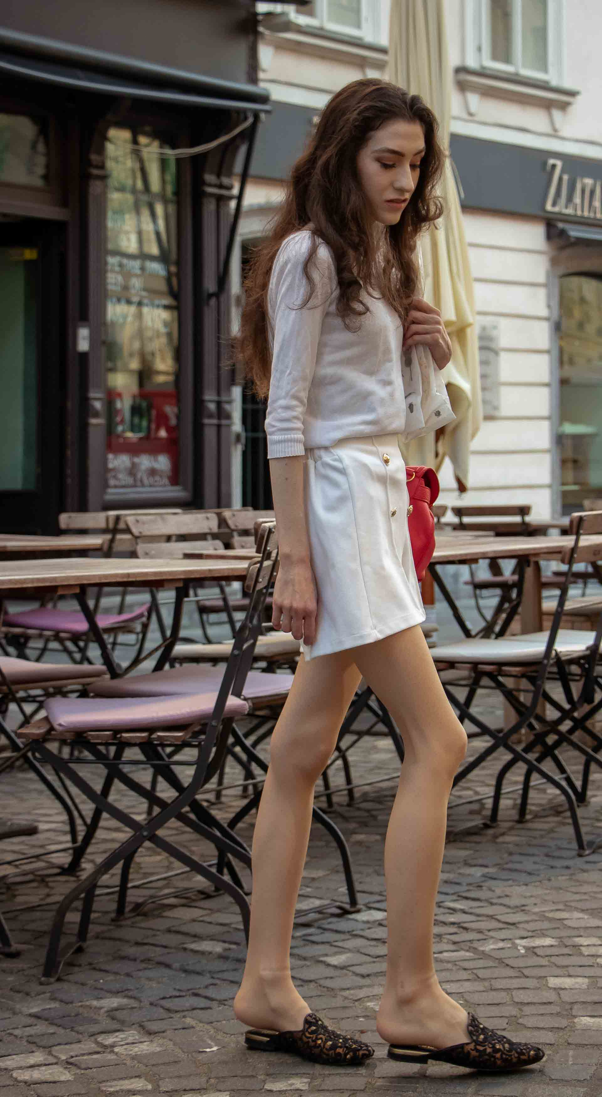 Beautiful Slovenian Fashion Blogger Veronika Lipar of Brunette from Wall wearing all in white outfit, a white sweater, white tailored shorts, black flat slipper mules, pink top handle bag, a paper bag in summer in the city