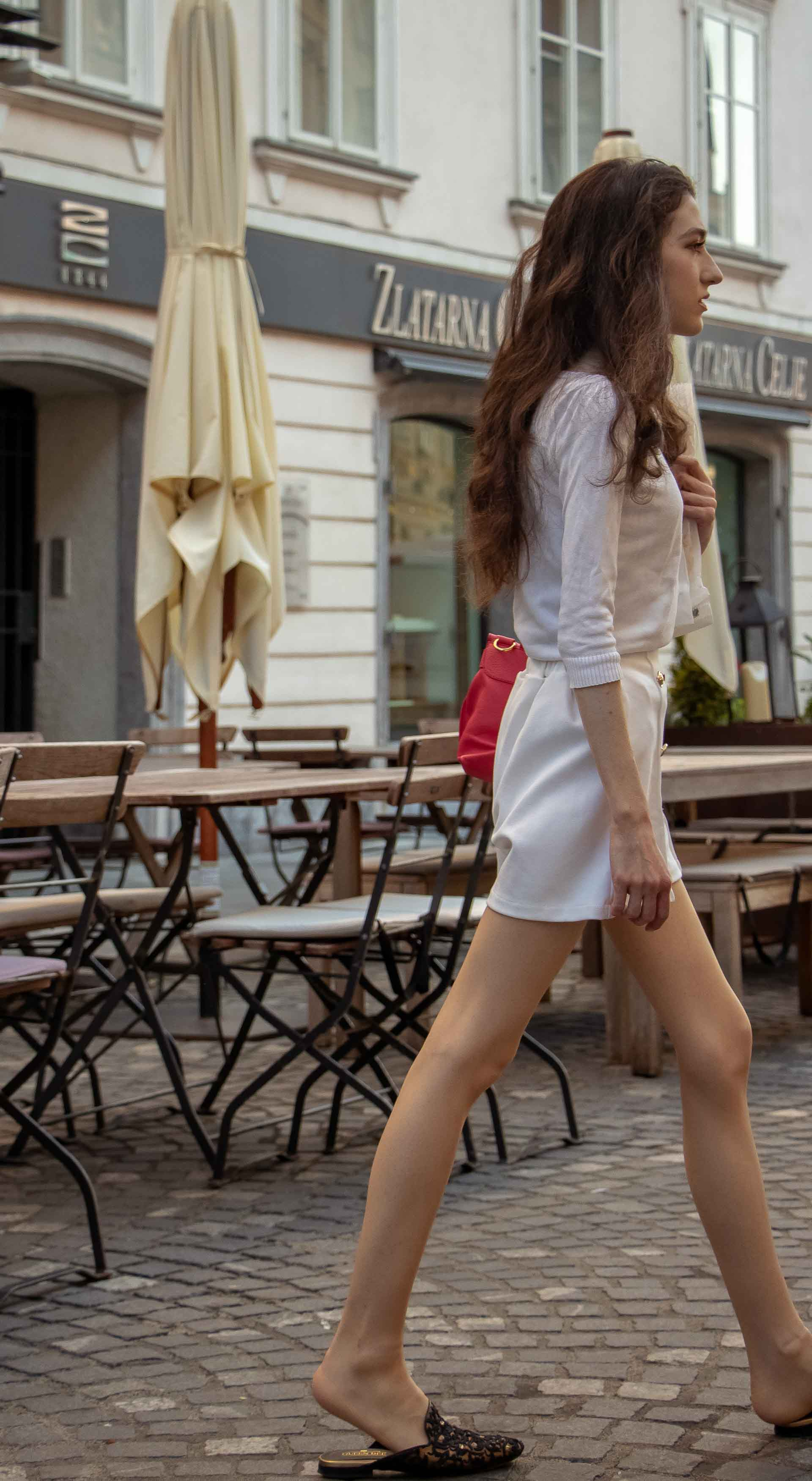 Beautiful Slovenian Fashion Blogger Veronika Lipar of Brunette from Wall wearing all in white outfit, a white sweater, white tailored shorts, black flat slipper mules, pink top handle bag, a paper bag while walking on the street in Ljubljana