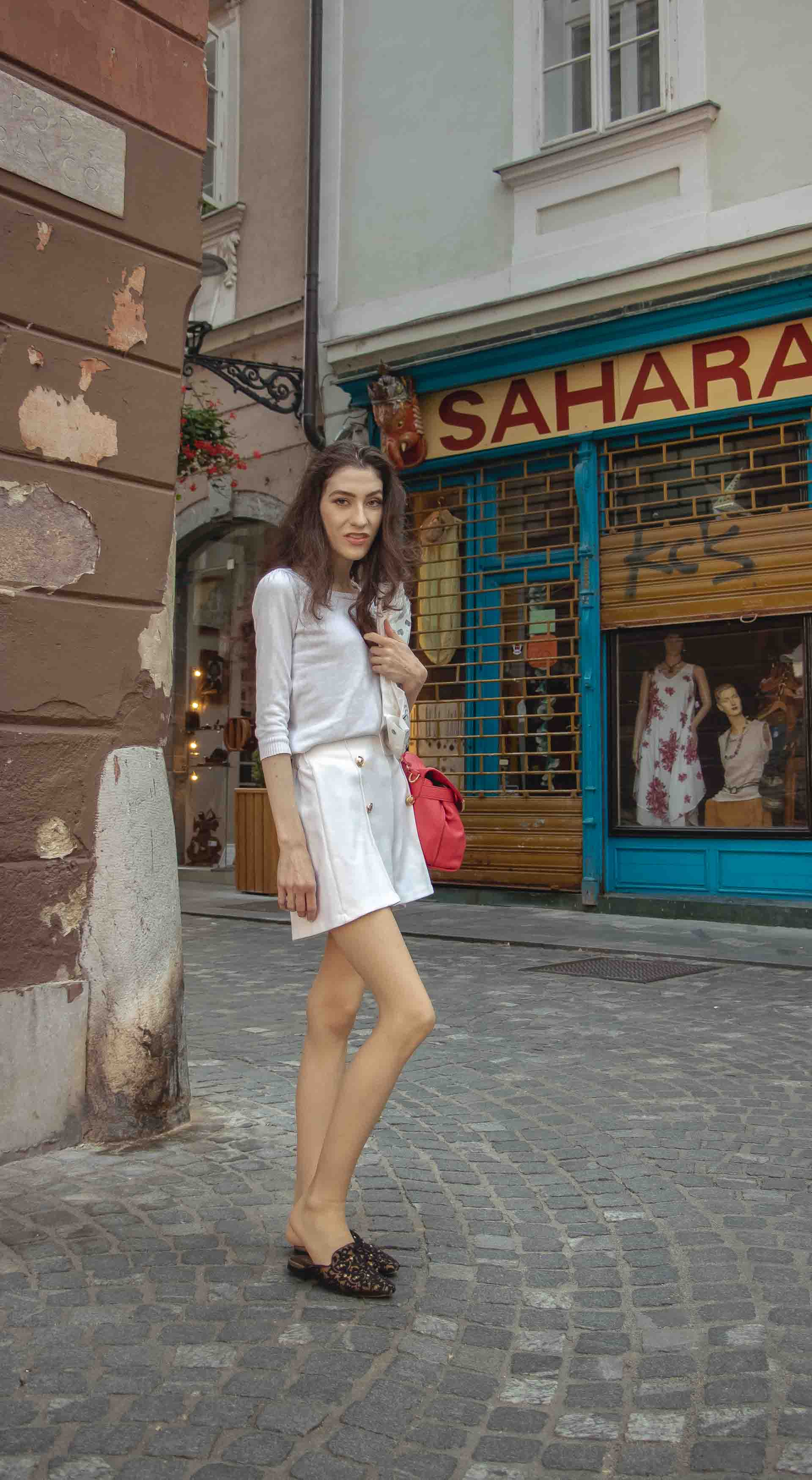 Beautiful Slovenian Fashion Blogger Veronika Lipar of Brunette from Wall dressed in all in white outfit, a white sweater, white tailored shorts, black flat slipper mules, pink top handle bag, a paper bag on the street in Ljubljana during heatwave
