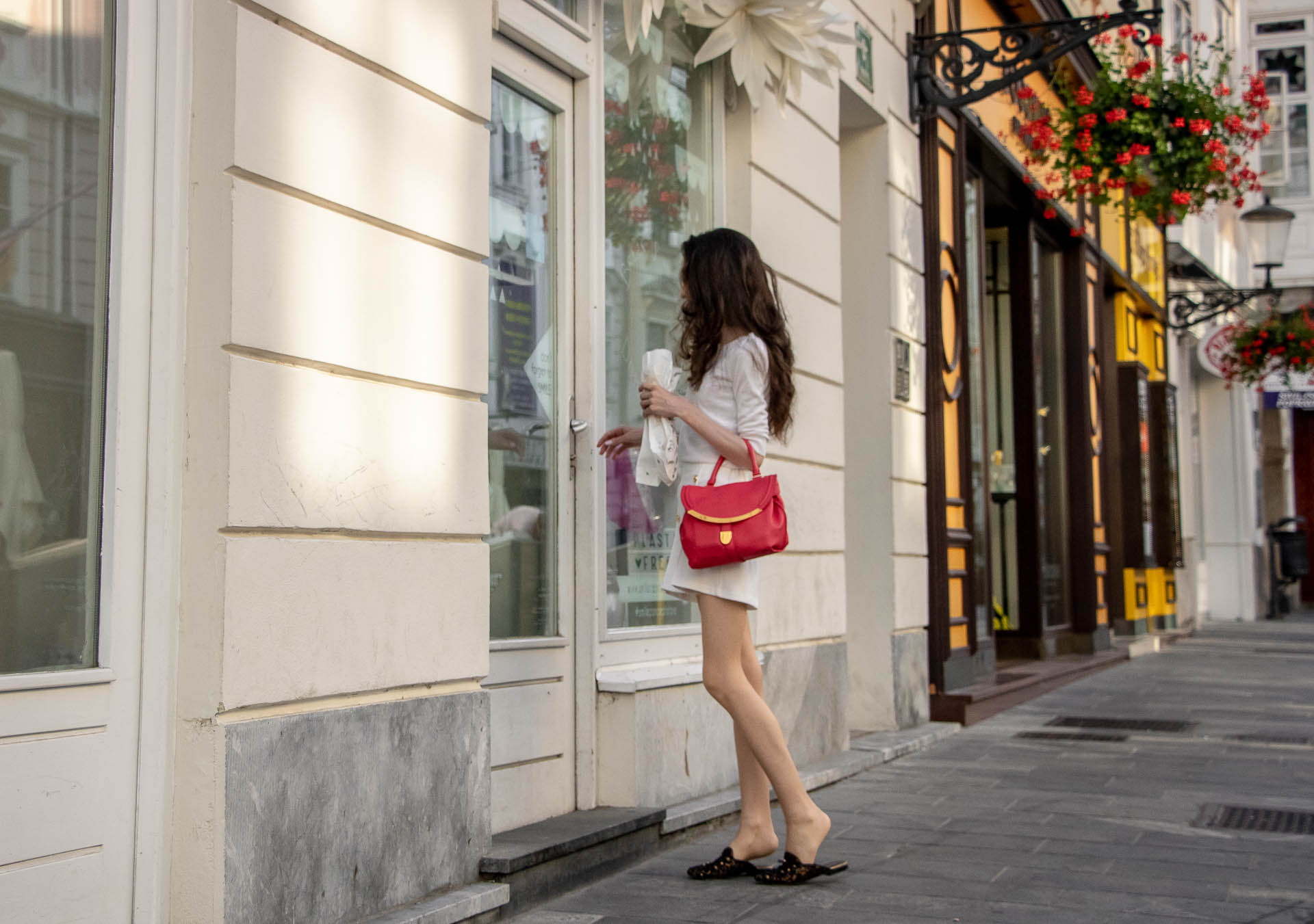 Beautiful Slovenian Fashion Blogger Veronika Lipar of Brunette from Wall wearing all in white outfit, a white sweater, white tailored shorts, black flat slipper mules, pink top handle bag, a paper bag on the street in Ljubljana when it's hot closing doors