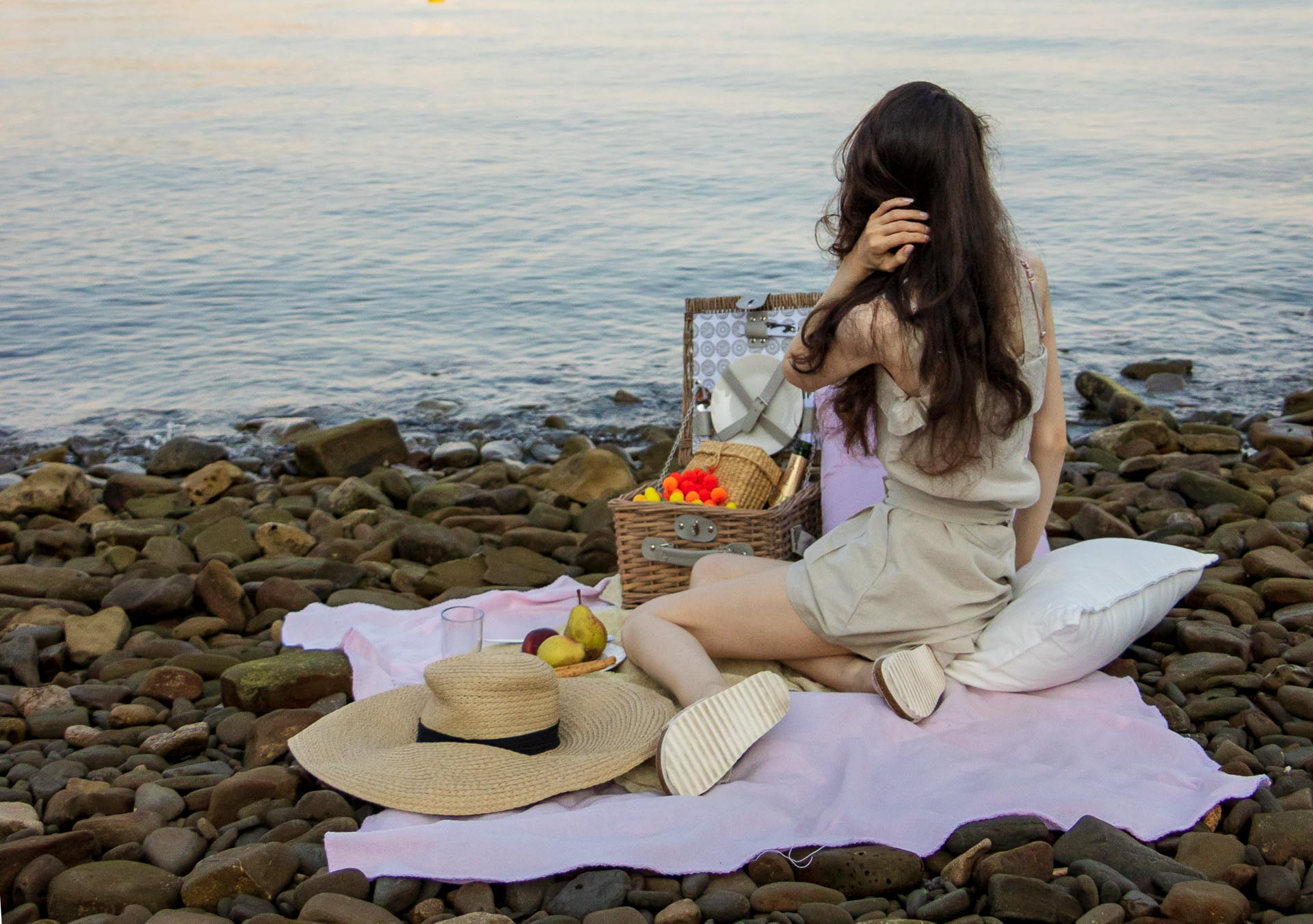Slovenian Fashion Blogger Veronika Lipar of Brunette from Wall dressed in beige linen crop top, paper bag linen shorts, luxe pool slides, large straw hat, Nannacay basket bag while having a beach picnic