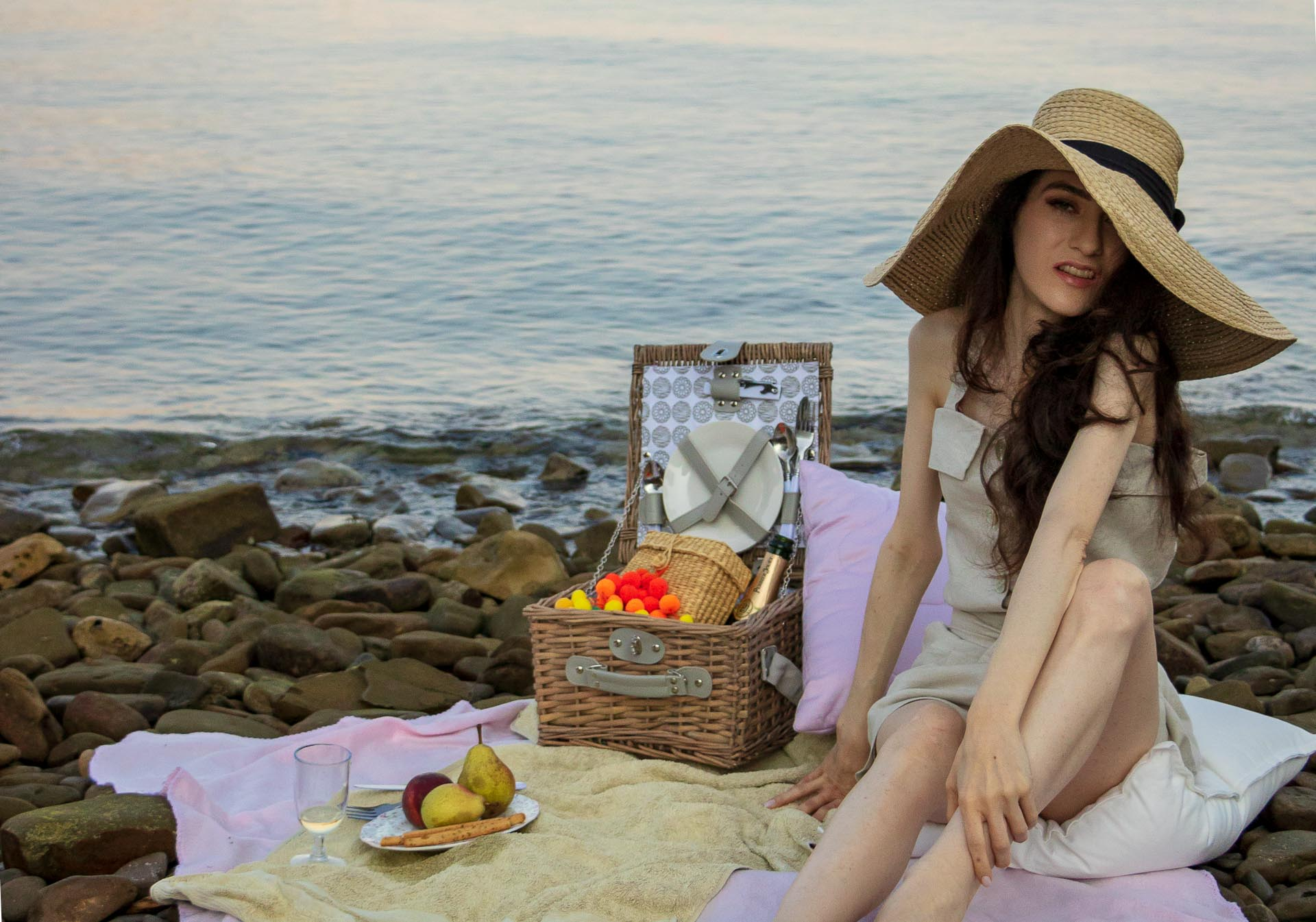 Slovenian Fashion Blogger Veronika Lipar of Brunette from Wall dressed in beige linen crop top, paper bag linen shorts, luxe pool slides, large straw hat, Nannacay basket bag while having beach picnic