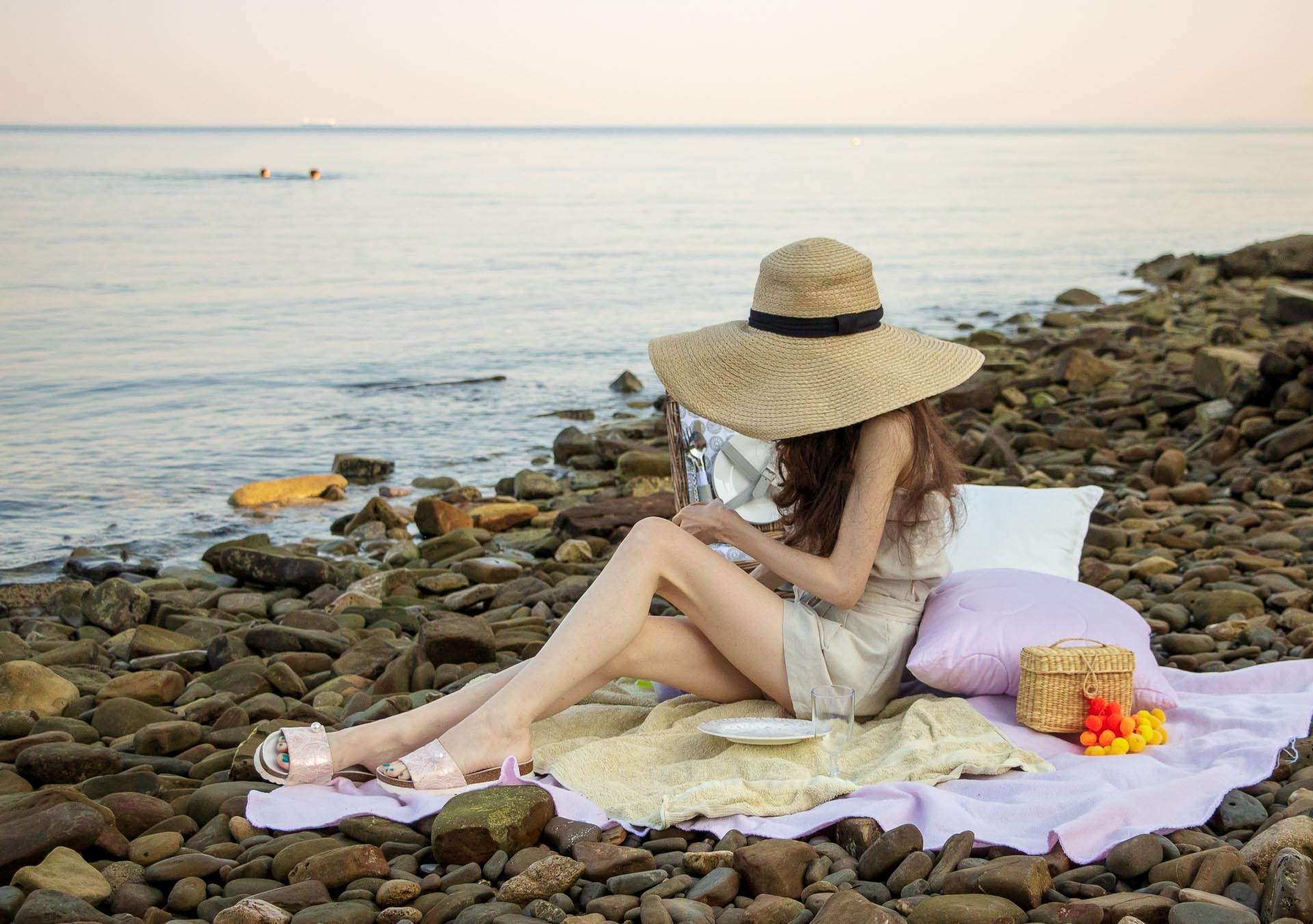 Slovenian Fashion Blogger Veronika Lipar of Brunette from Wall wearing beige linen crop top, paper bag linen shorts, luxe pool slides, large straw hat, Nannacay basket bag while sitting on the picnic blanket on the beach