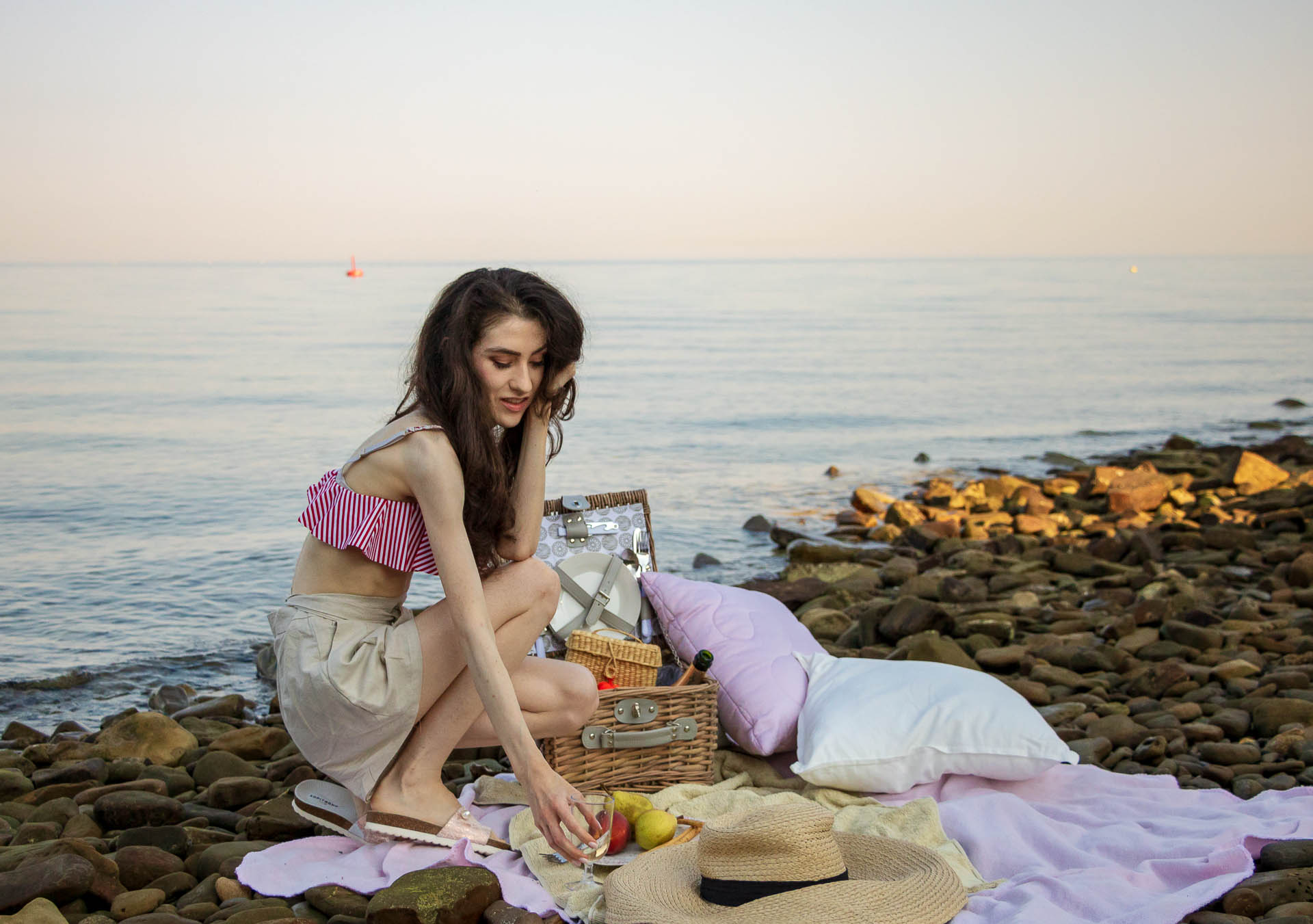 Slovenian Fashion Blogger Veronika Lipar of Brunette from Wall wearing beige linen crop top, paper bag linen shorts, luxe pool slides, large straw hat, Nannacay basket bag while pouring champagne for beach picnic