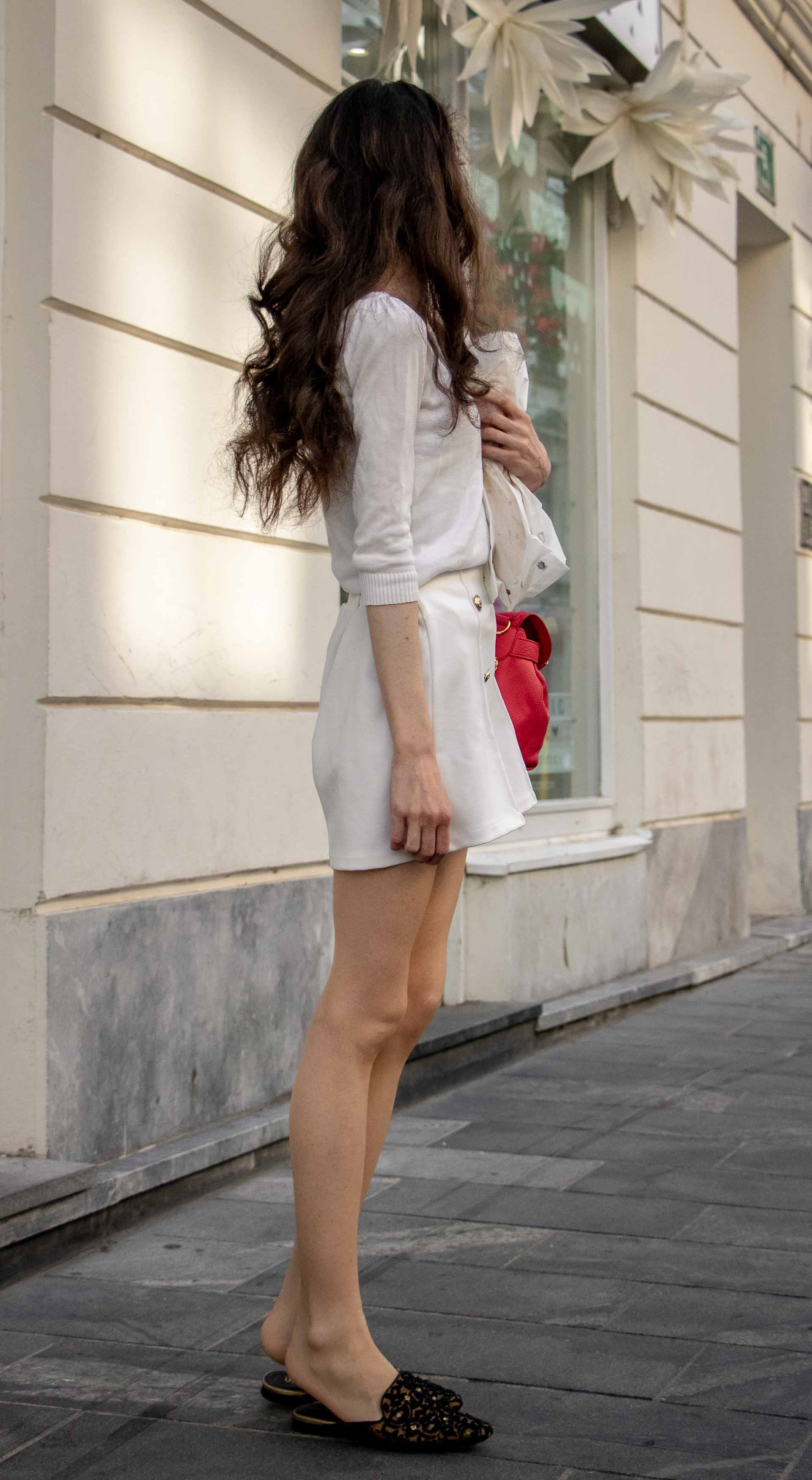 Beautiful Slovenian Fashion Blogger Veronika Lipar of Brunette from Wall dressed in all in white outfit, a white sweater, white tailored shorts, black flat slipper mules, pink top handle bag, a paper bag when it's hot