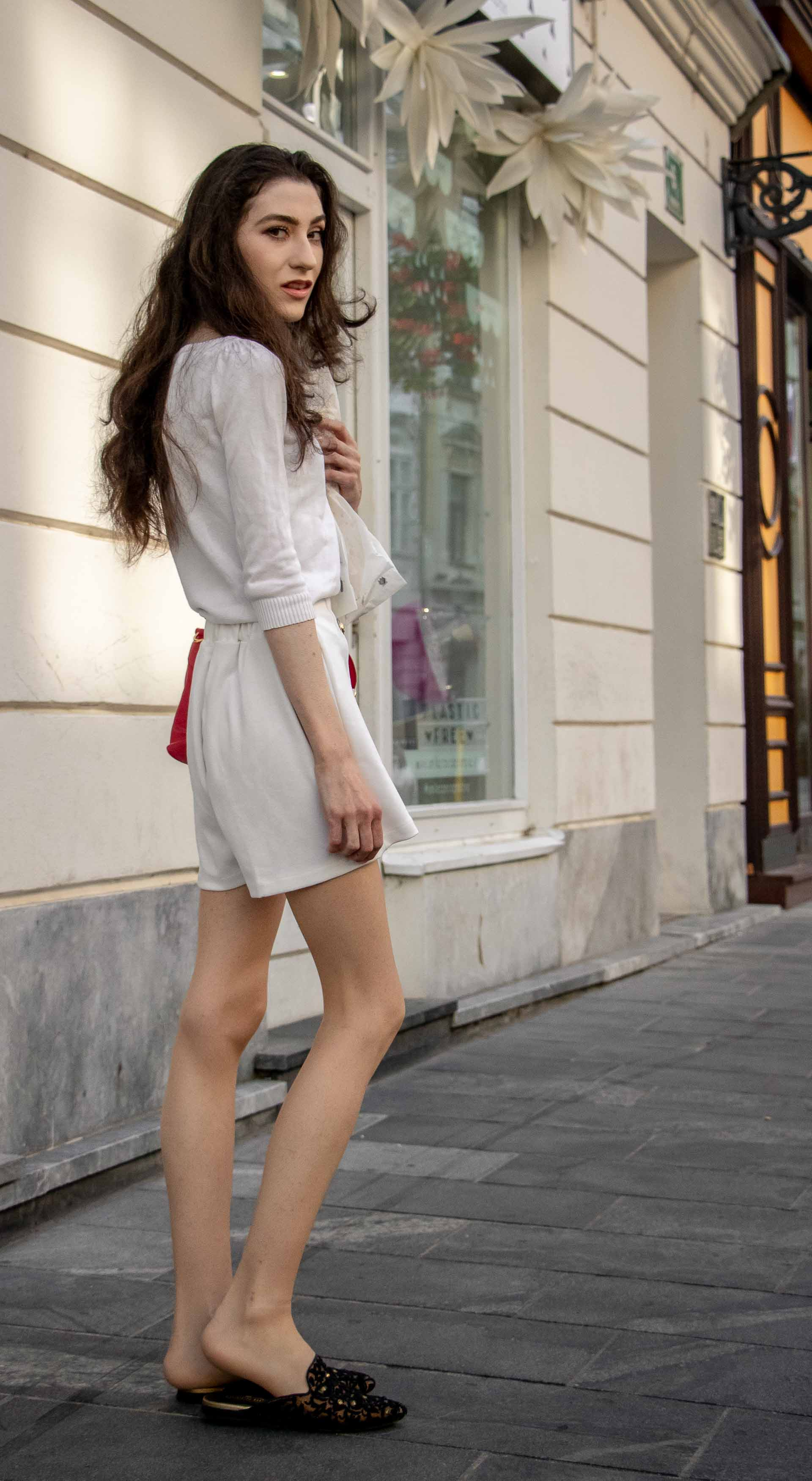 Beautiful Slovenian Fashion Blogger Veronika Lipar of Brunette from Wall dressed in all in white outfit, a white sweater, white tailored shorts, black flat slipper mules, pink top handle bag, a paper bag while on the street in Ljubljana