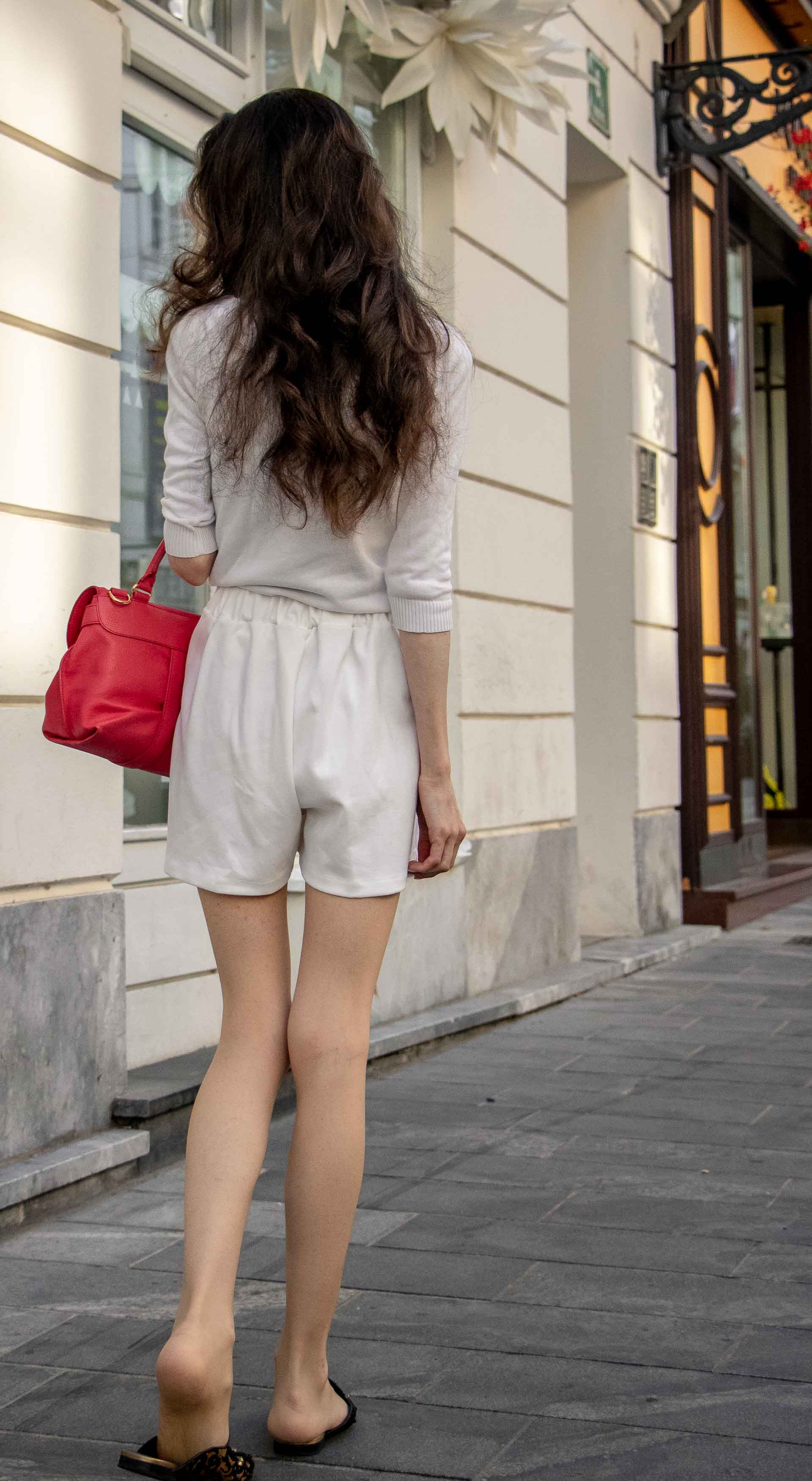 Beautiful Slovenian Fashion Blogger Veronika Lipar of Brunette from Wall dressed in all in white outfit, a white sweater, white tailored shorts, black flat slipper mules, pink top handle bag, a paper bag on the street in Ljubljana