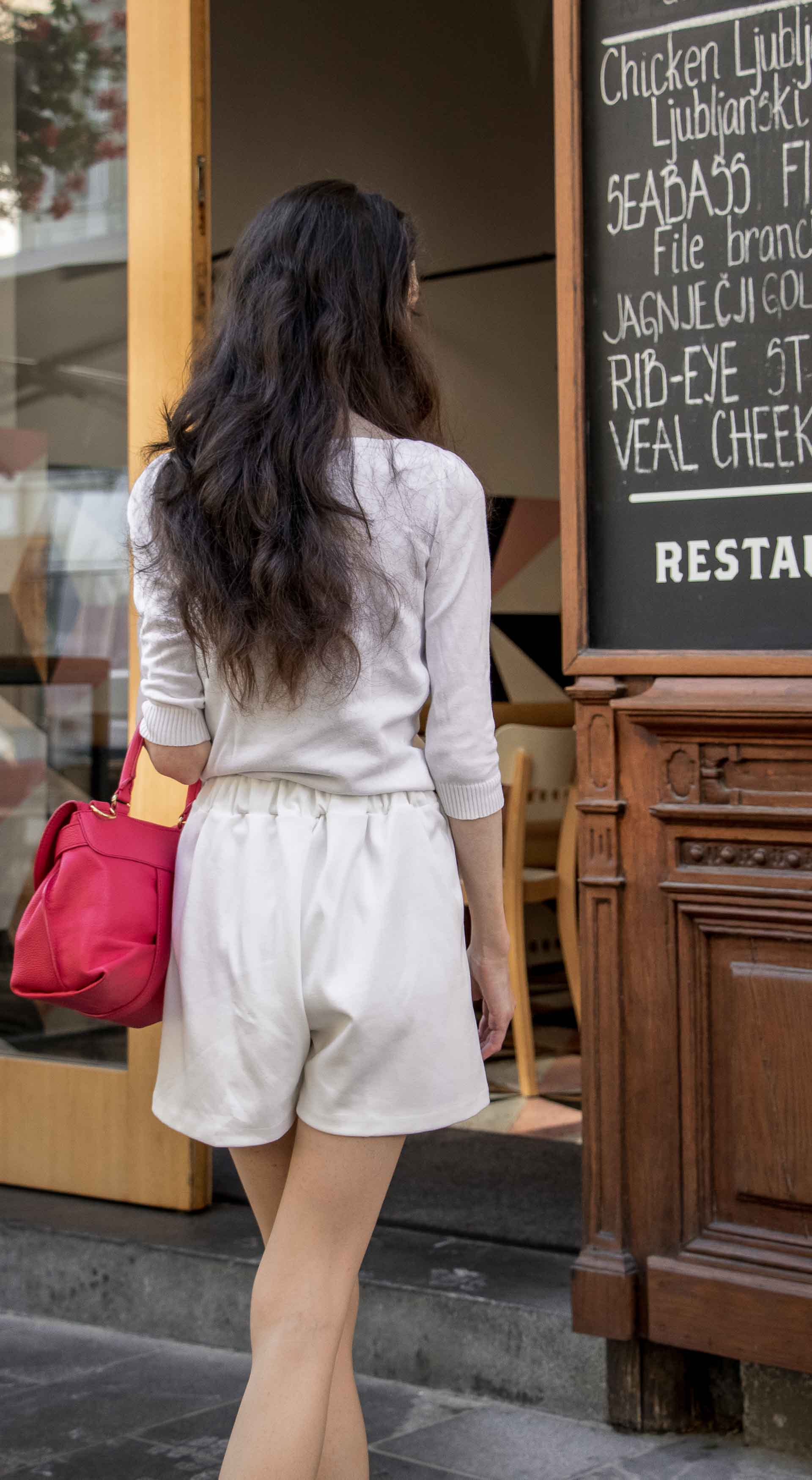 Slovenska modna blogerka Veronika Lipar of Brunette from Wall wearing all in white outfit, a white sweater, white tailored shorts, black flat slipper mules, pink top handle bag, a paper bag on the street in Ljubljana when reading the menu on a table