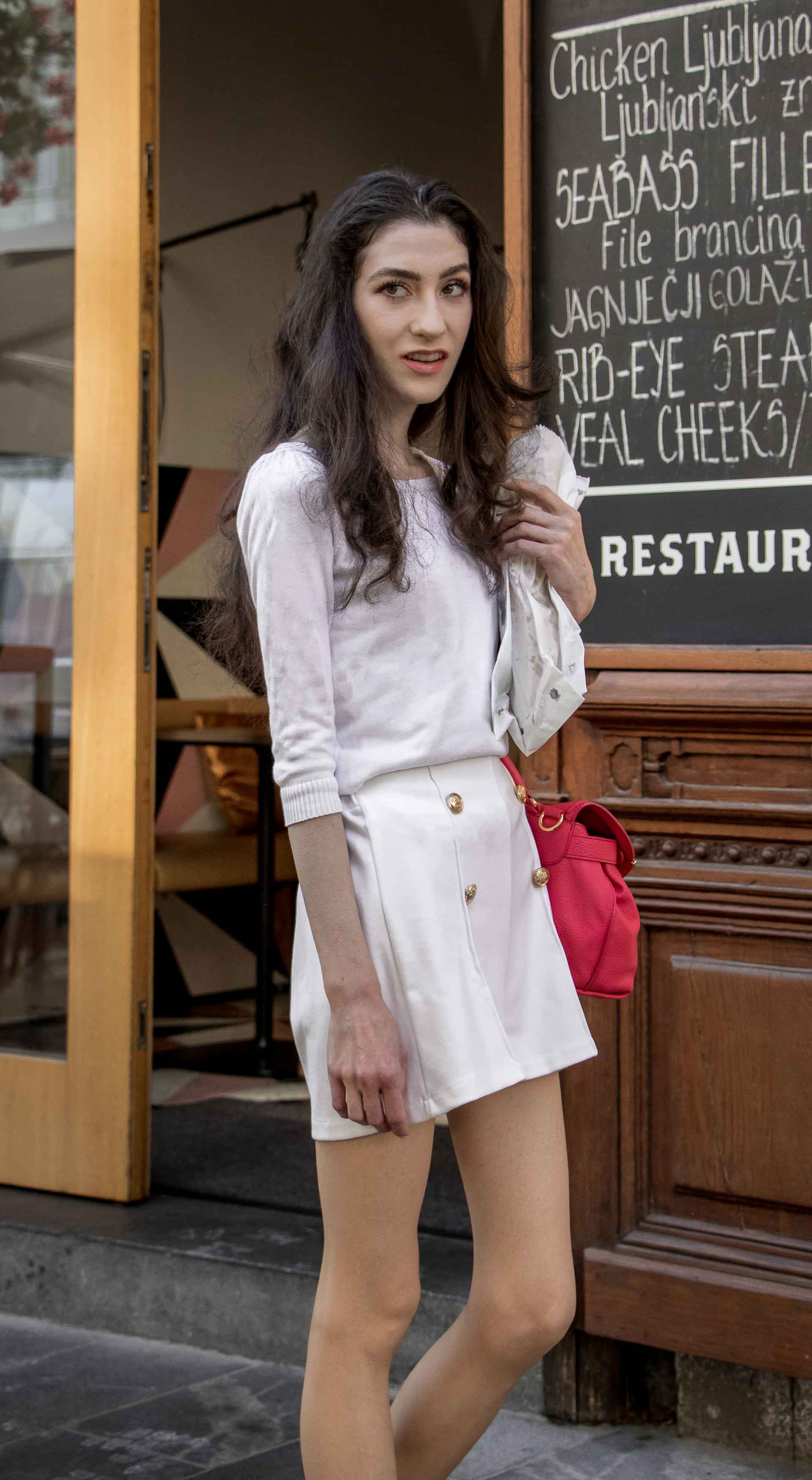 Slovenska modna blogerka Veronika Lipar of Brunette from Wall wearing all in white outfit, a white sweater, white tailored shorts, black flat slipper mules, pink top handle bag, a paper bag during heat wave in Ljubljana