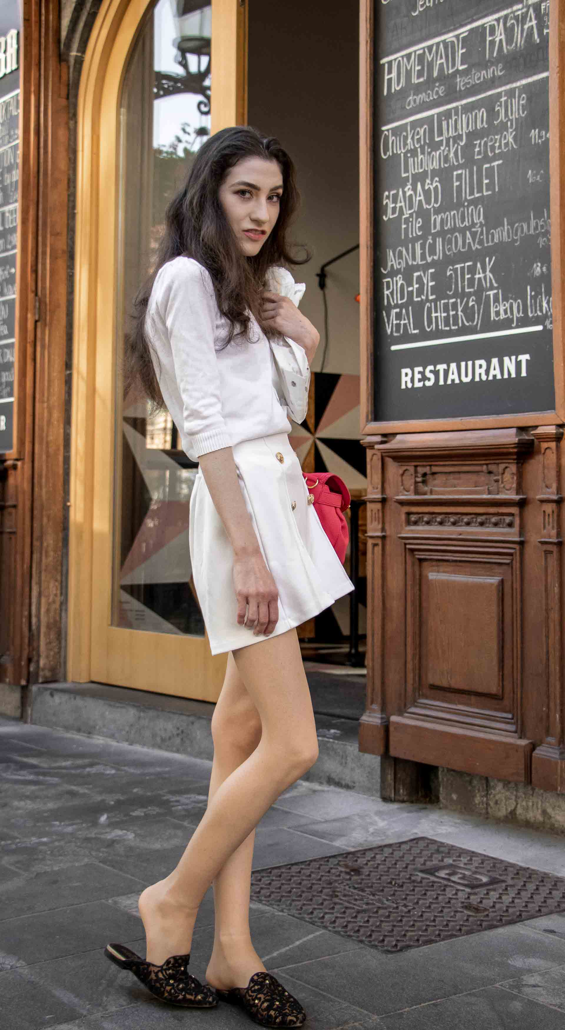 Slovenska modna blogerka Veronika Lipar of Brunette from Wall wearing all in white outfit, a white sweater, white tailored shorts, black flat slipper mules, pink top handle bag, a paper bag on the street in Ljubljana