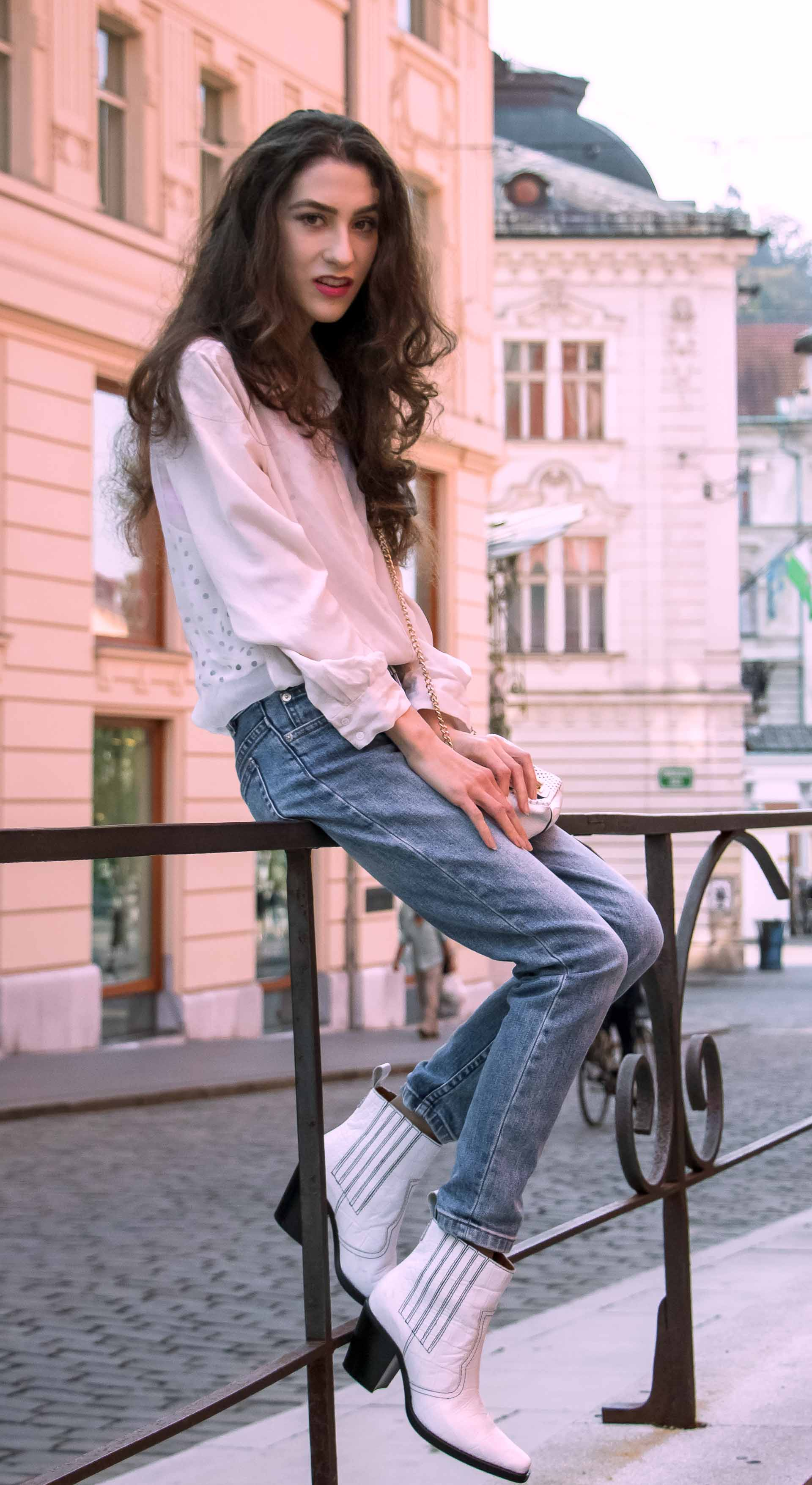 Beautiful Slovenian Fashion Blogger Veronika Lipar of Brunette from Wall dressed in white silk shirt from Sandro Paris, white and black polka dot cami slip top, A.P.C. light blue jeans, white Ganni Western boots, chain strap shoulder bag sitting on the fence in Ljubljana