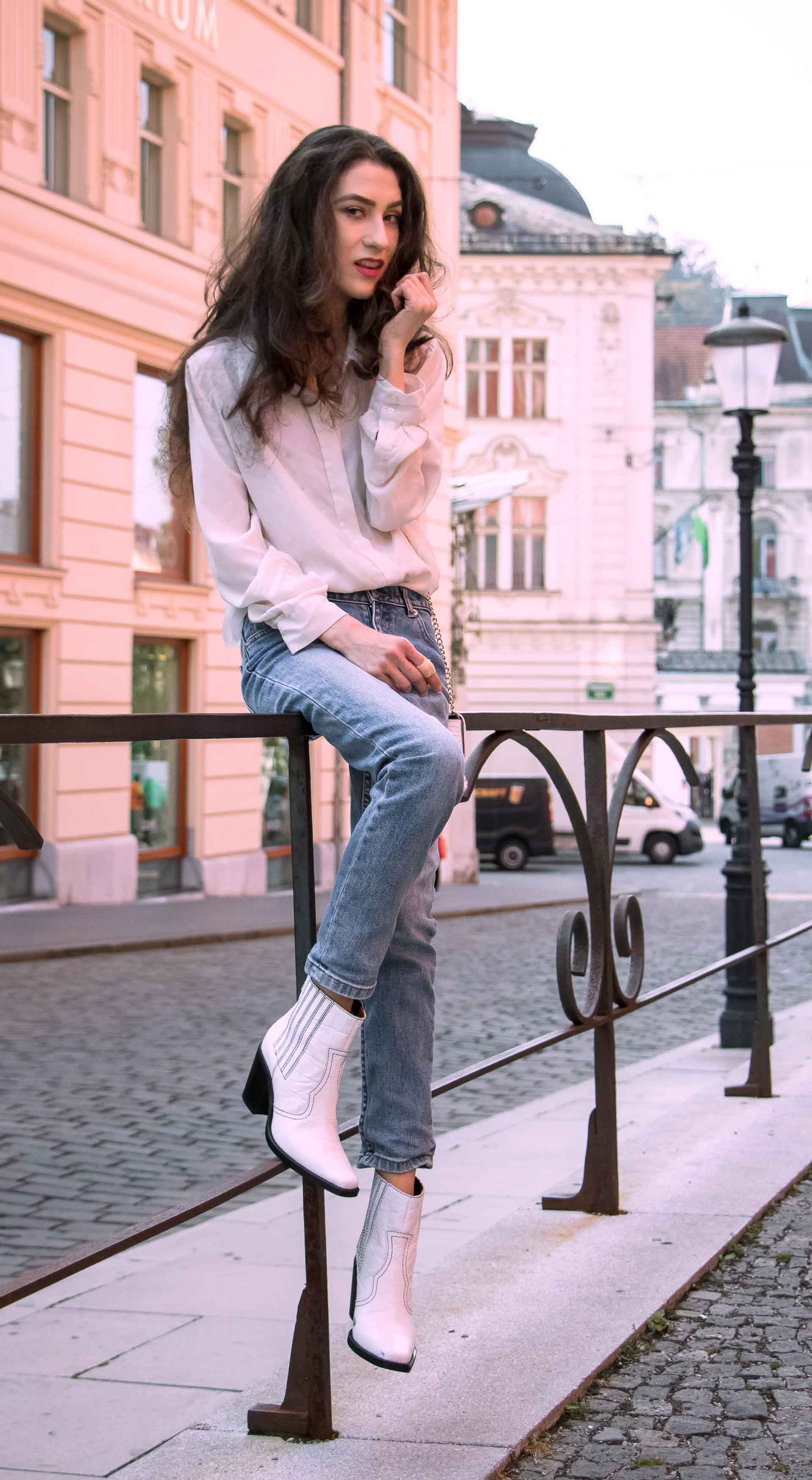 Beautiful Slovenian Fashion Blogger Veronika Lipar of Brunette from Wall wearing chic everyday outfit white silk shirt from Sandro Paris, white and black polka dot cami slip top, A.P.C. light blue jeans, white Ganni Western boots, chain strap shoulder bag sitting on the fence in Ljubljana