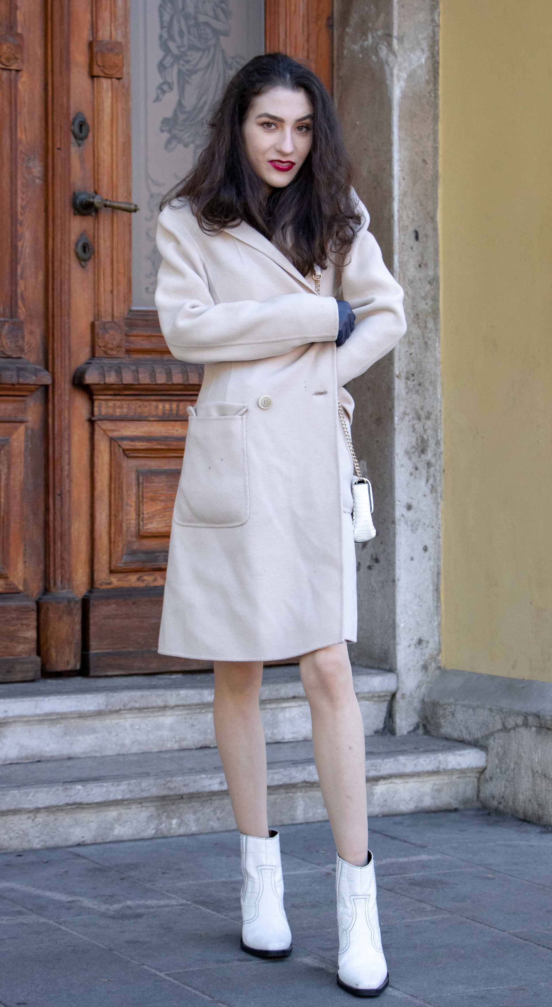 Beautiful Slovenian Fashion Blogger Veronika Lipar of Brunette from Wall dressed in off-white double breasted Max Mara coat with white Ganni cowboy boots, white chain shoulder bag in morning on the street in Ljubljana