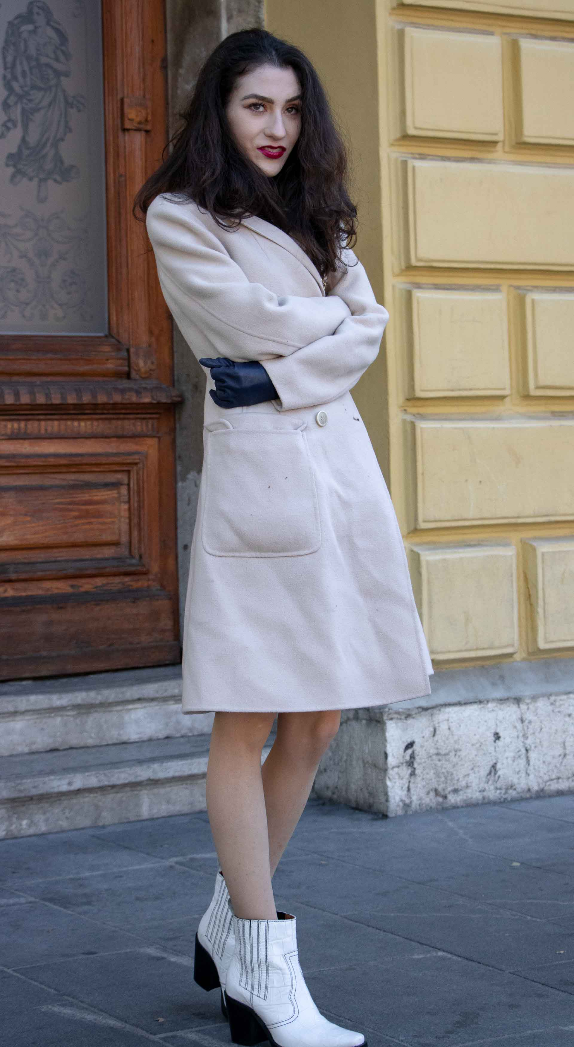 Beautiful Slovenian Fashion Blogger Veronika Lipar of Brunette from Wall wrapped in off-white double breasted Max Mara coat with white Ganni cowboy boots, white chain shoulder bag in morning on the street in Ljubljana
