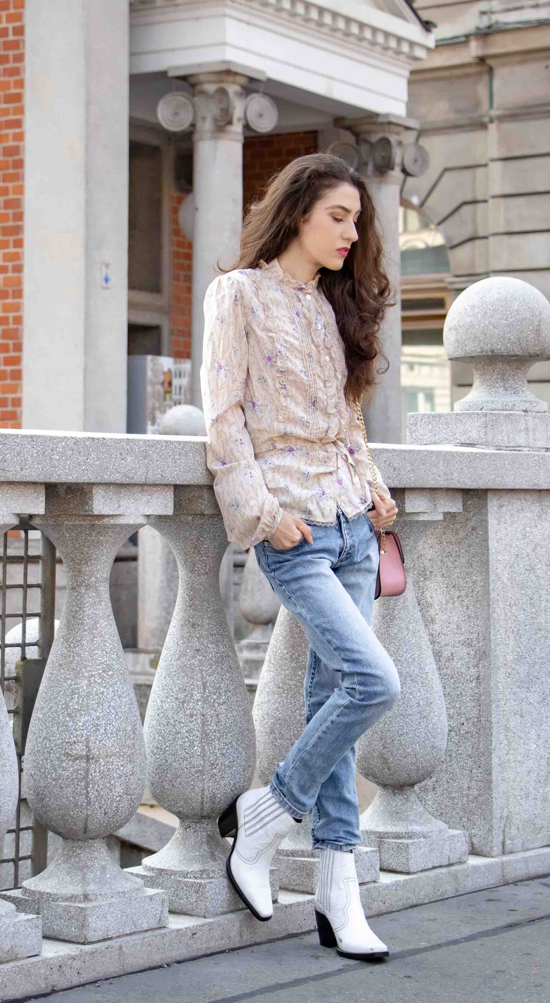 Beautiful Slovenian Fashion Blogger Veronika Lipar of Brunette from Wall dressed in white Ganni Western boots, floral long sleeved Prairie blouse, A.P.C. blue jeans on the street in fall in Ljubljana