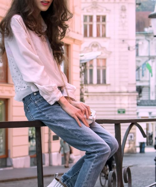 Beautiful Slovenian Fashion Blogger Veronika Lipar of Brunette from Wall wearing white silk shirt from Sandro Paris, white and black polka dot cami slip top, A.P.C. light blue jeans, white Ganni Western boots, chain strap shoulder bag sitting on the fence in Ljubljana