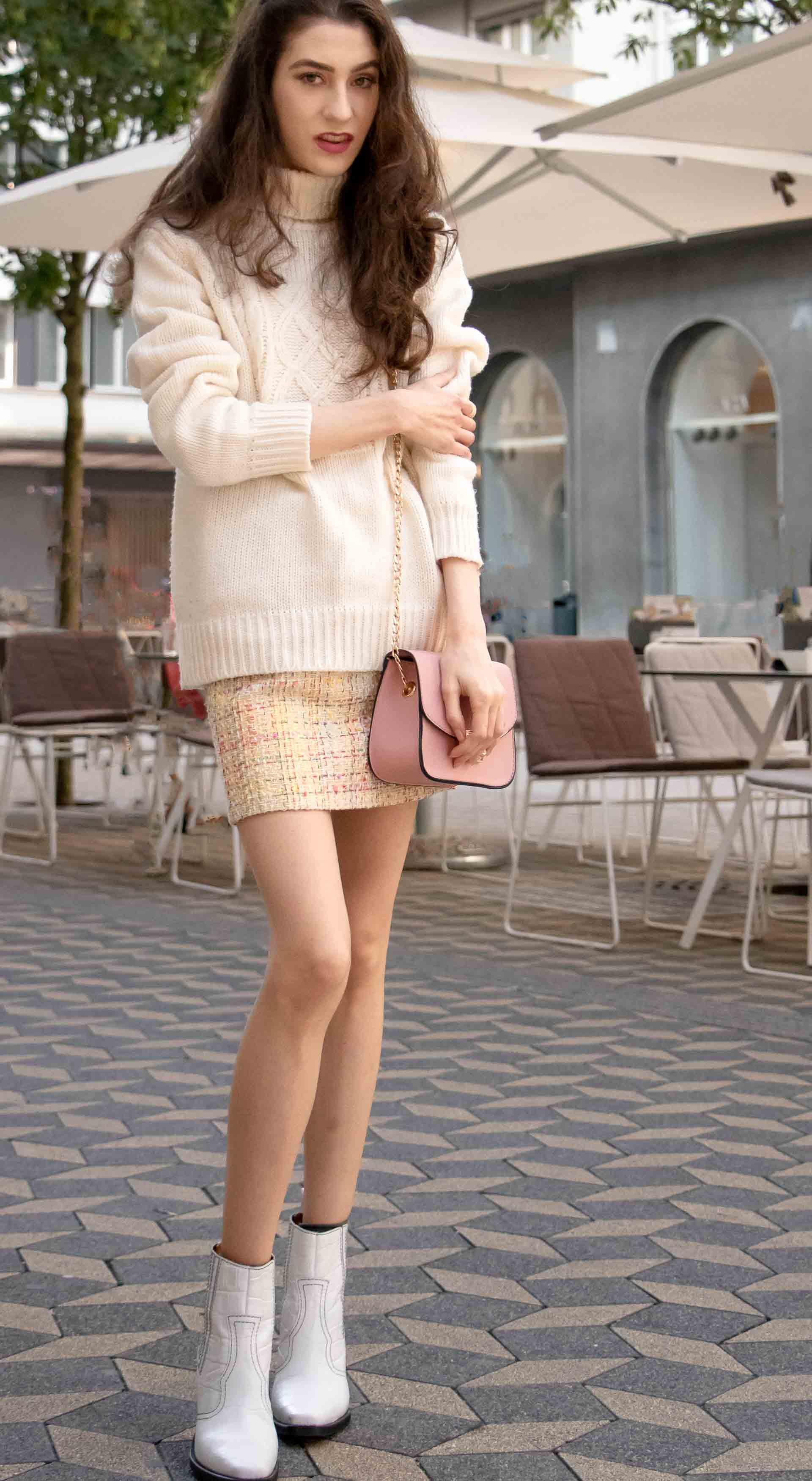 Beautiful Slovenian Fashion Blogger Veronika Lipar of Brunette from Wall wearing white Ganni Western boots, yellow tweed skirt, white turtleneck sweater, chain strap shoulder bag for autumn brunch