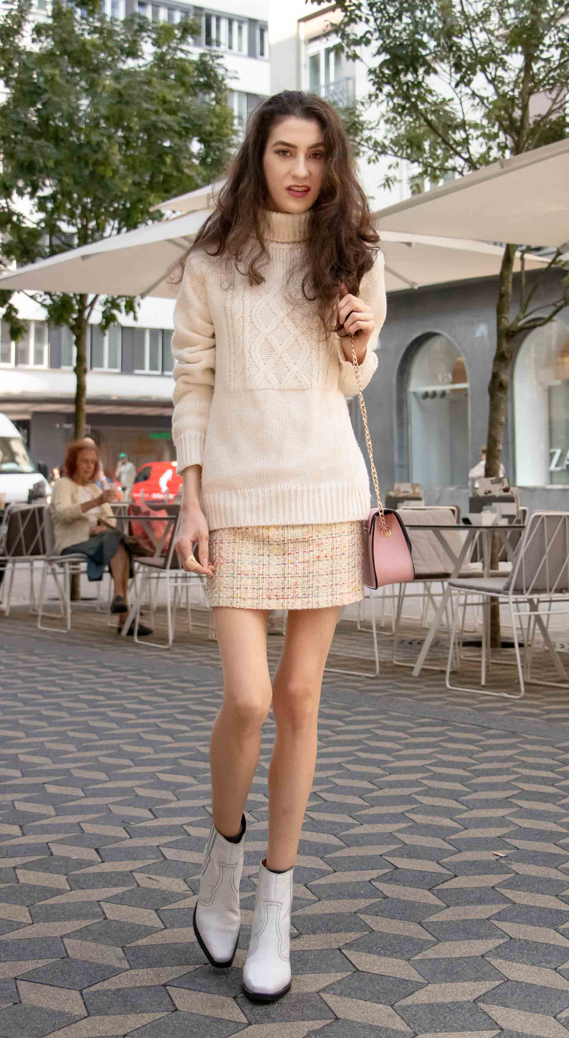Beautiful Slovenian Fashion Blogger Veronika Lipar of Brunette from Wall dressed in white Ganni Western boots, yellow tweed skirt, white turtleneck sweater, chain strap shoulder bag for fall brunch