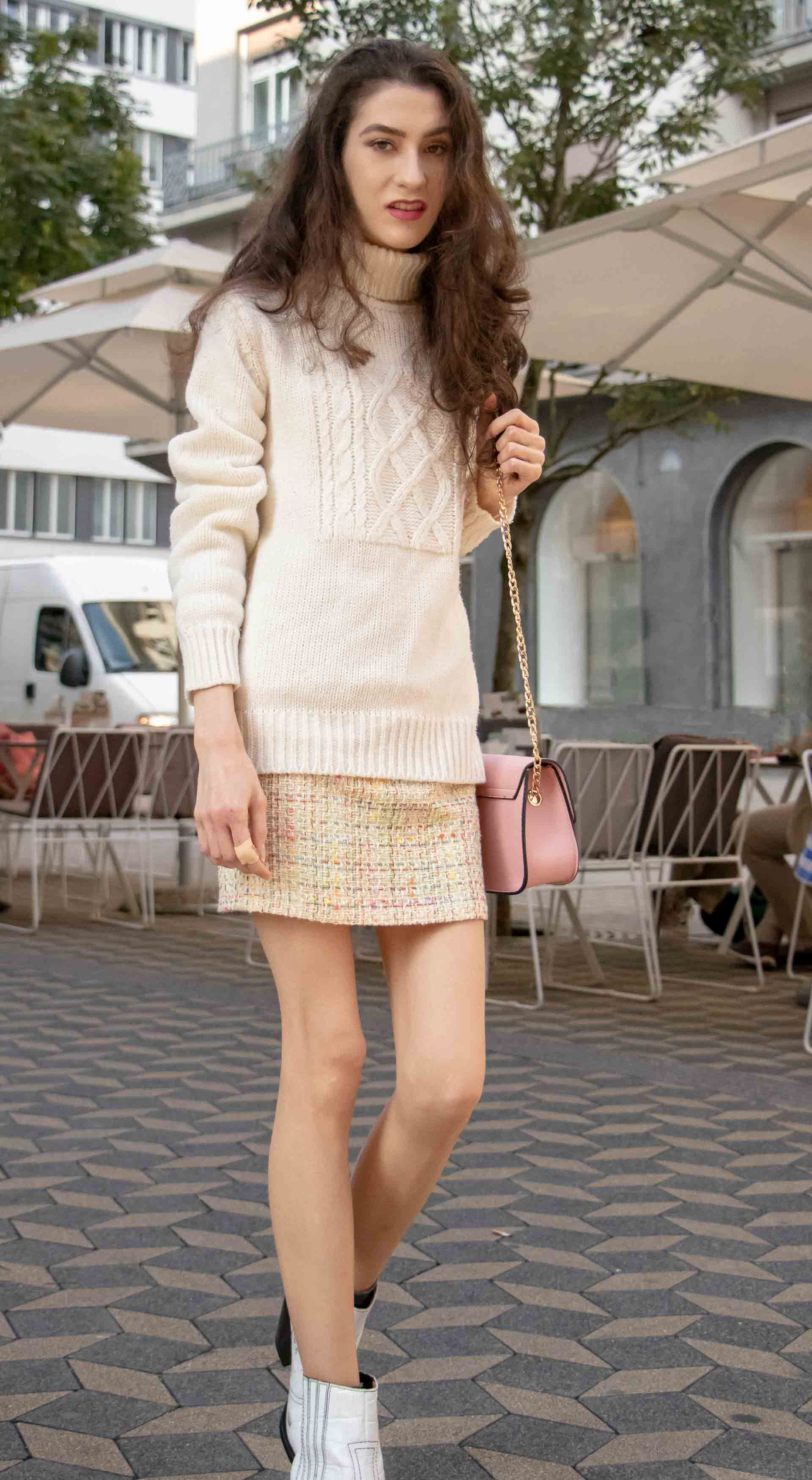 Beautiful Slovenian Fashion Blogger Veronika Lipar of Brunette from Wall dressed in white Ganni Western boots, yellow tweed skirt, white turtleneck sweater, chain strap shoulder bag for brunch on the street in the morning in Ljubljana in fall
